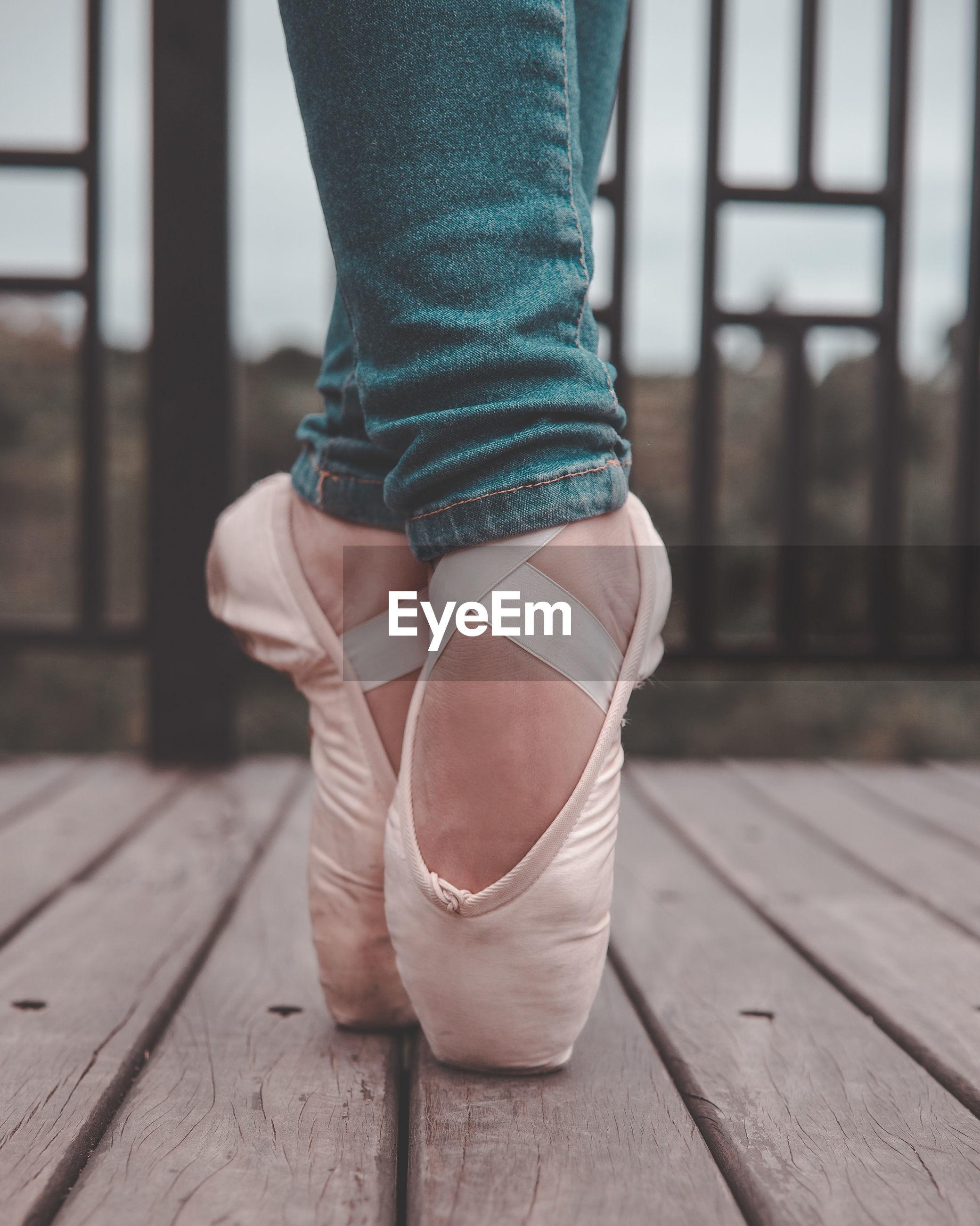 Low section of ballet dancing on wooden floor