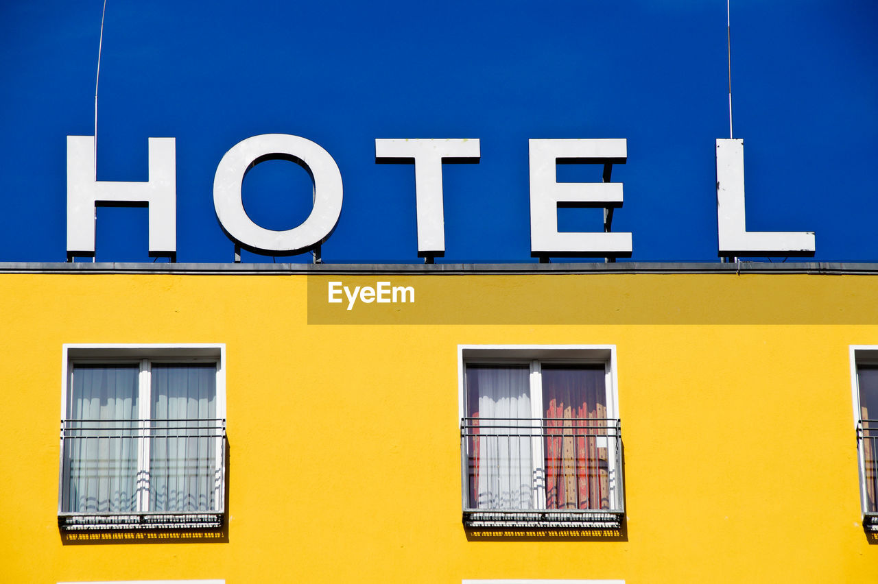 Low Angle View Of Hotel Text On Yellow Building Against Blue Sky