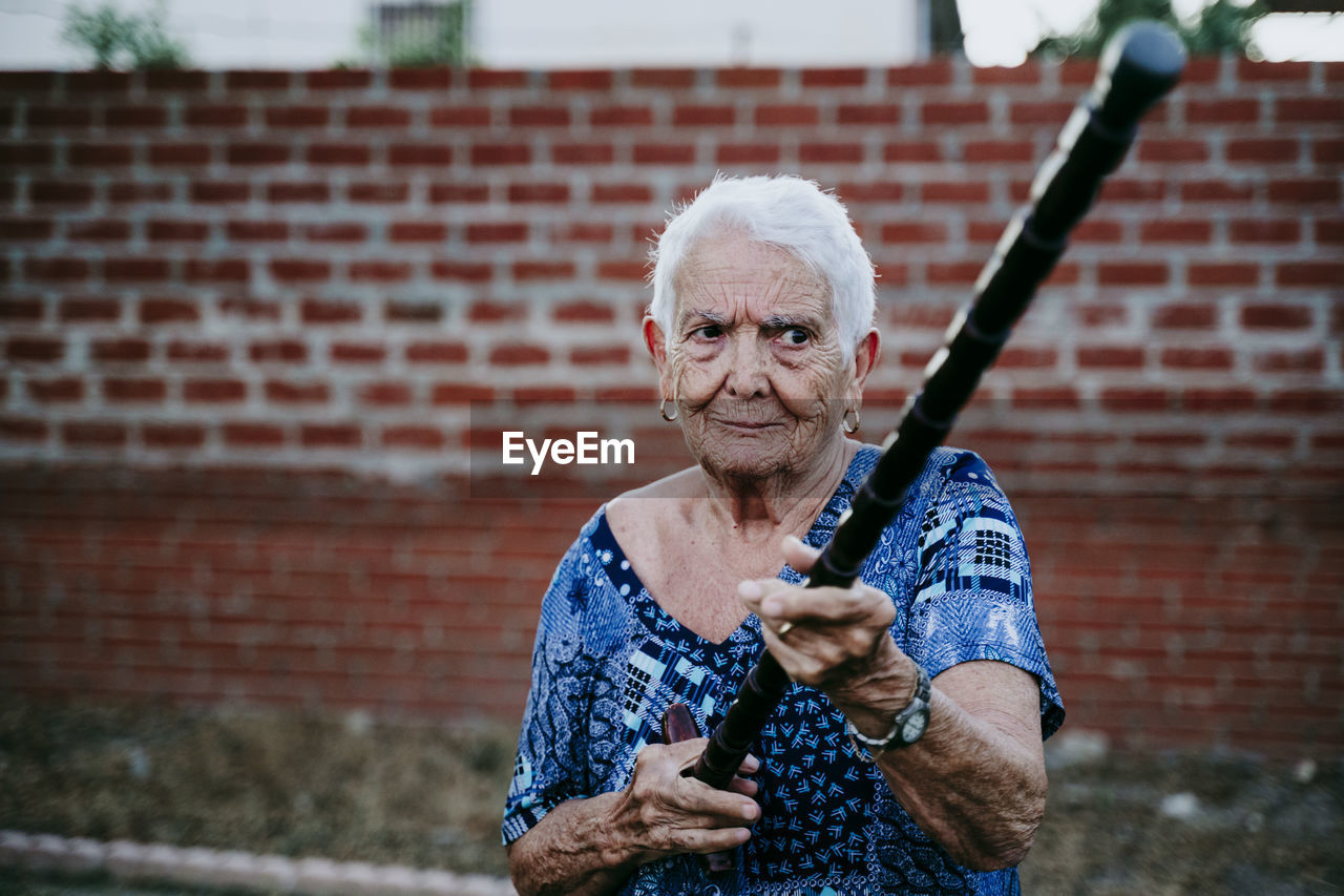 Senior woman holding stick against brick wall