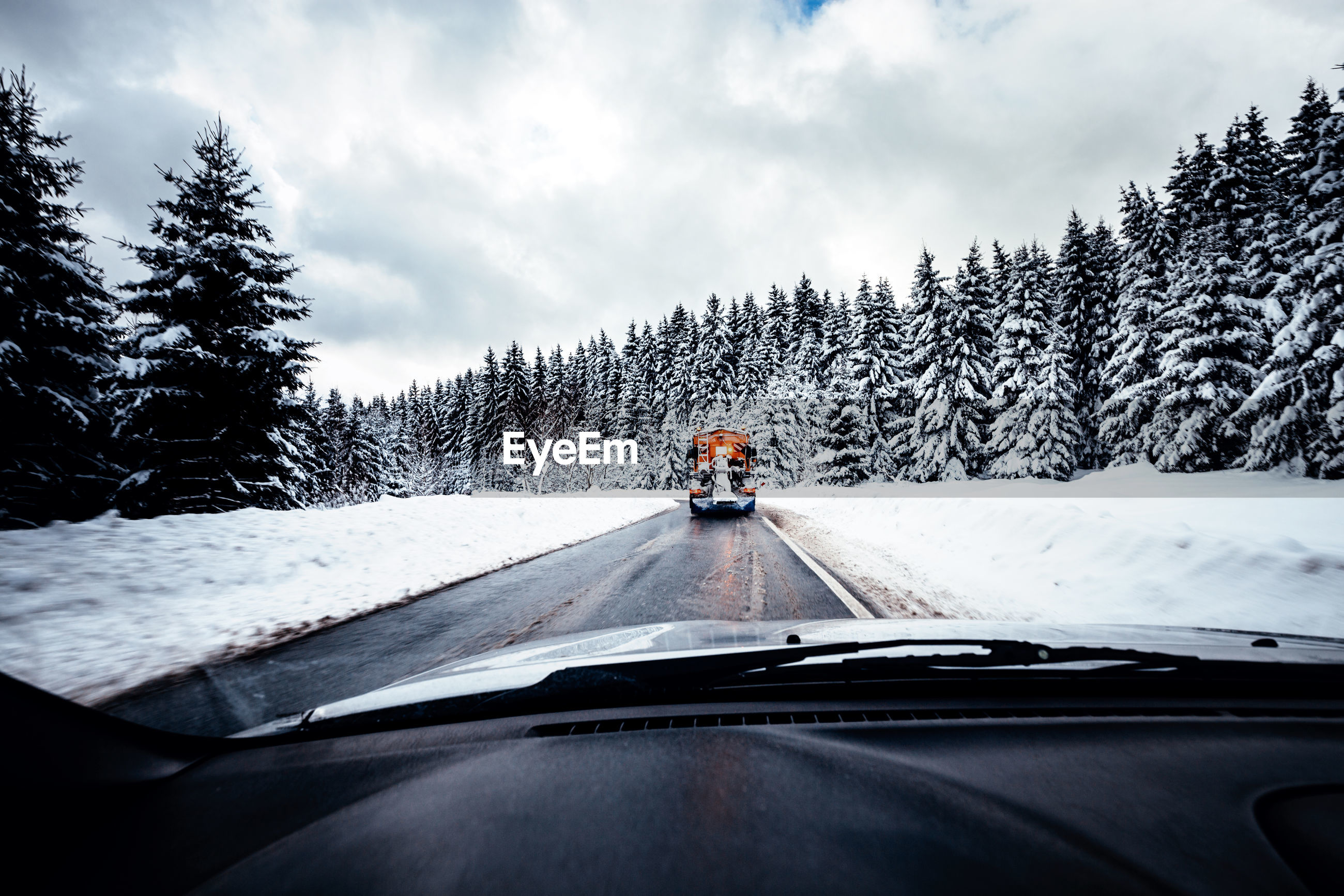 Truck seen through car windshield on road during winter