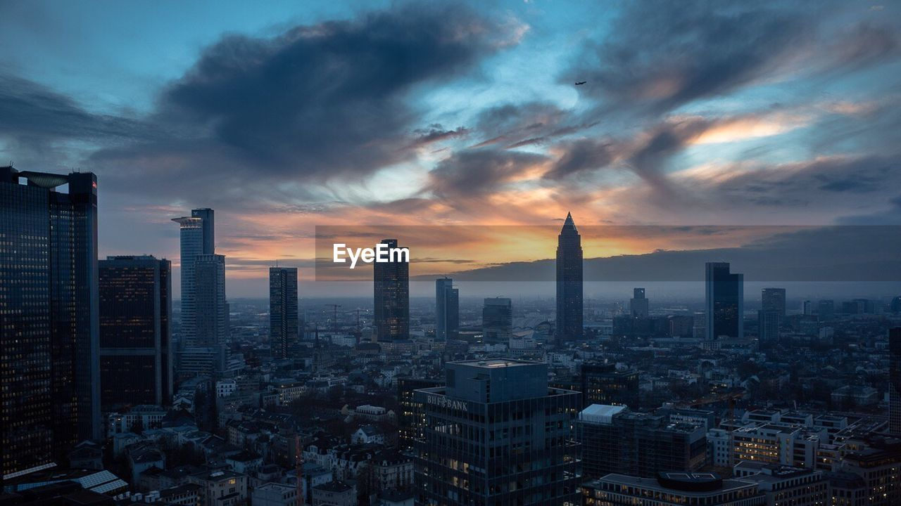 skyscraper, architecture, cityscape, building exterior, sky, tall - high, sunset, cloud - sky, city, built structure, tower, modern, travel destinations, no people, urban skyline, outdoors, nature, day