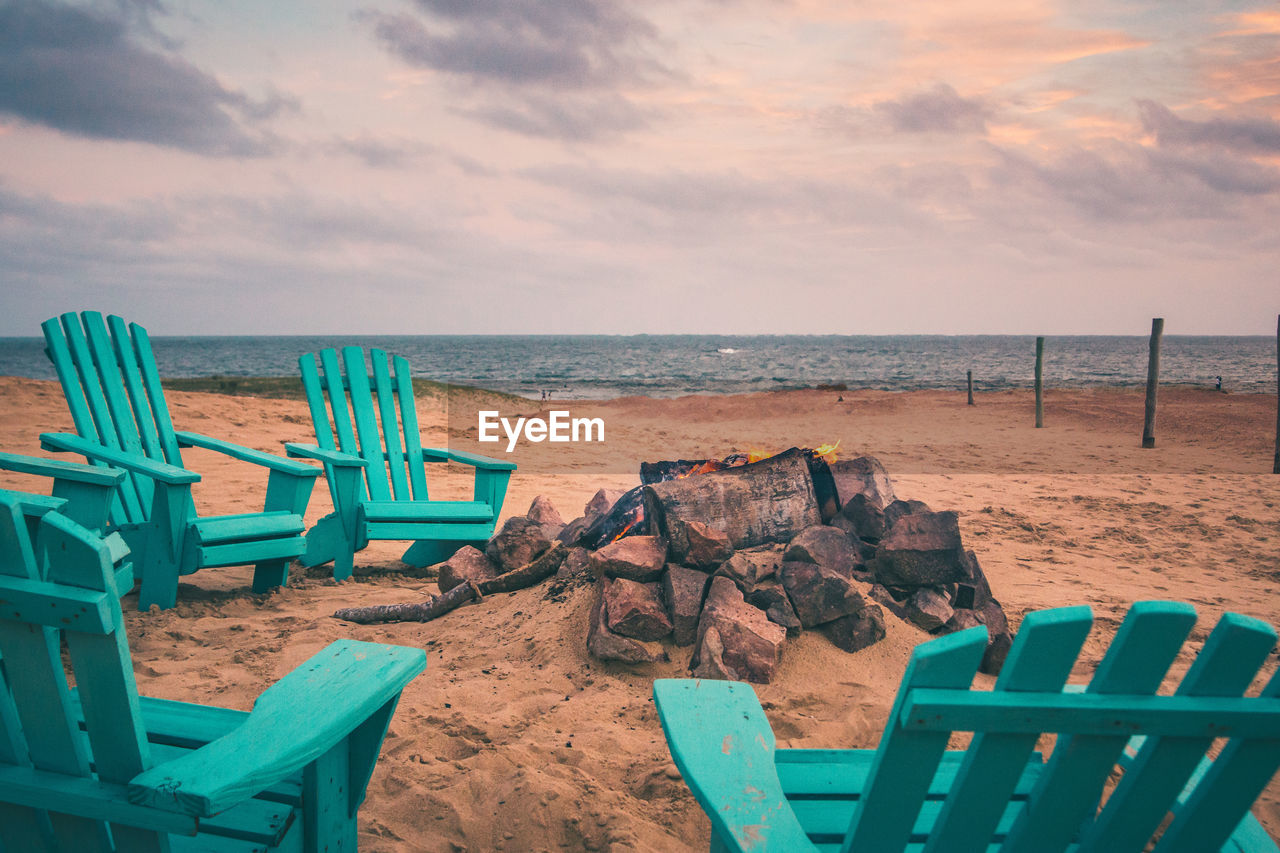 Wooden Chairs On Beach Against Sky During Sunset