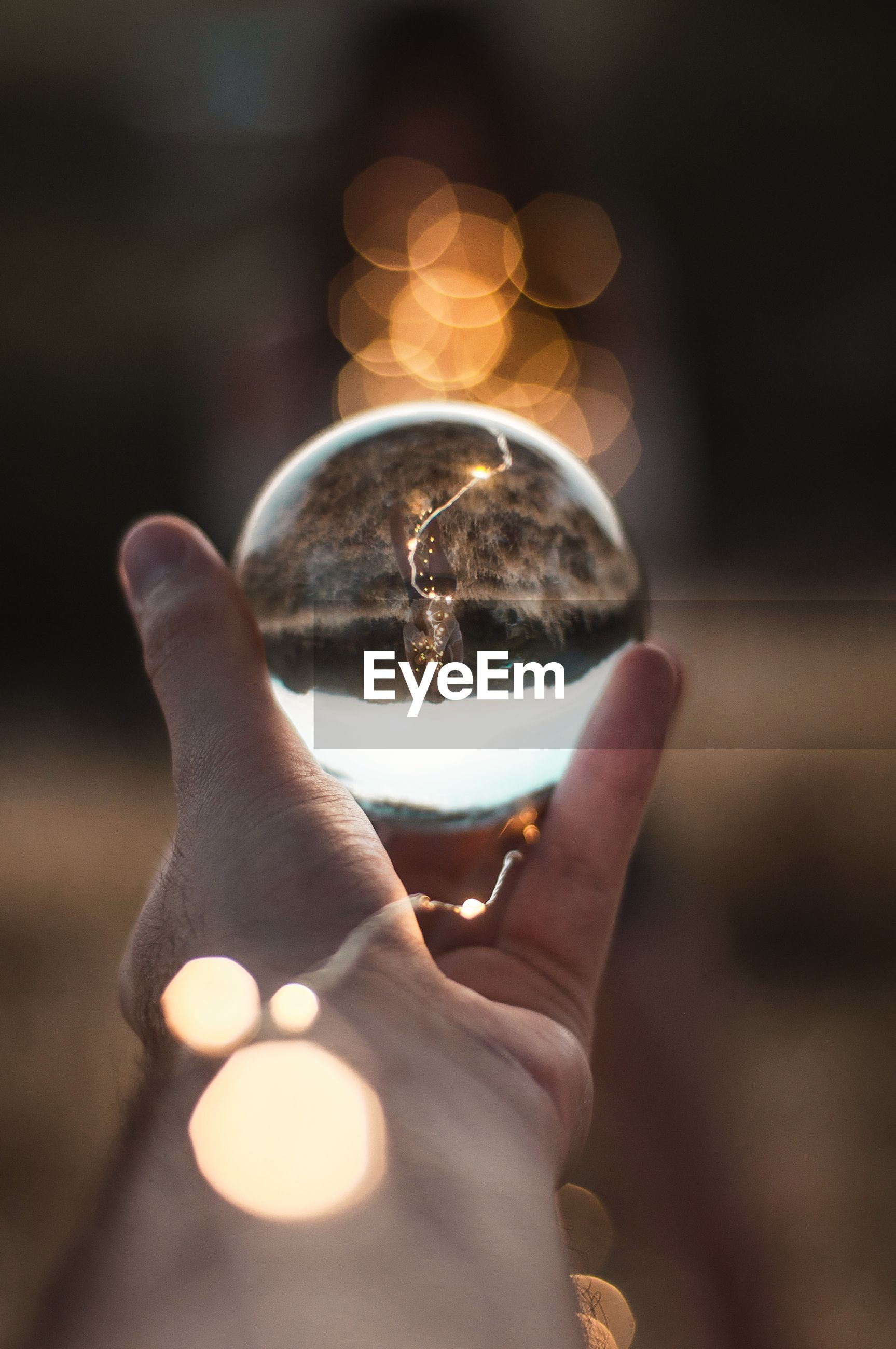 Close-up of cropped hand holding crystal ball with reflection