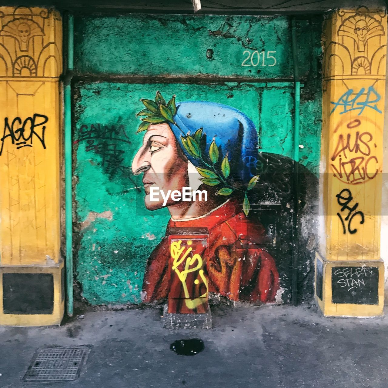 text, human representation, art and craft, communication, graffiti, creativity, representation, male likeness, architecture, one person, built structure, day, wall - building feature, real people, door, multi colored, entrance, female likeness, non-western script