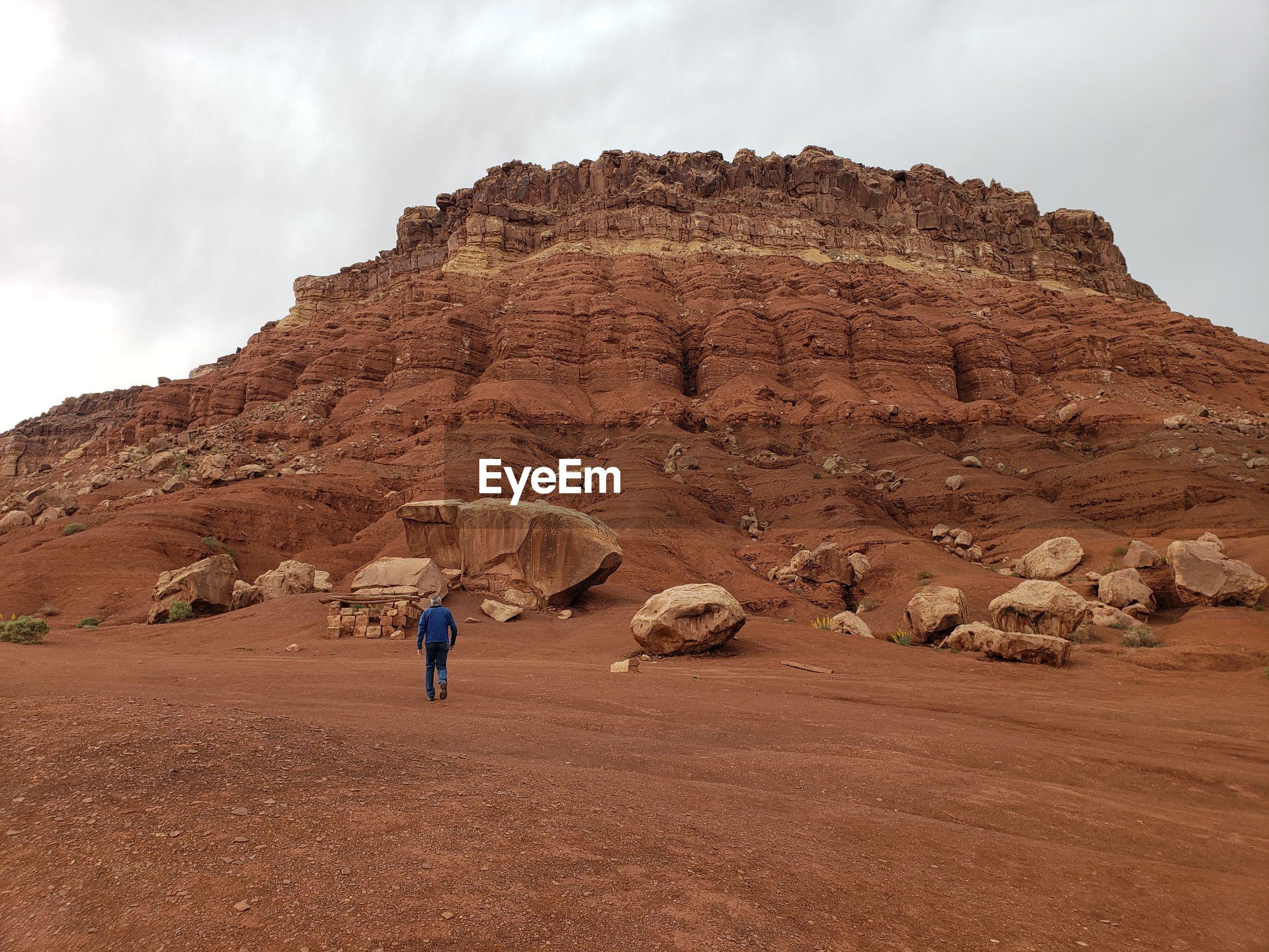 Rear view of man walking in desert towards rock formations