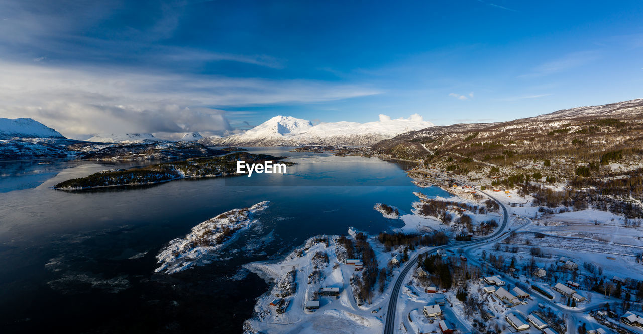 Scenic view of snowcapped mountains and lake against sky during winter