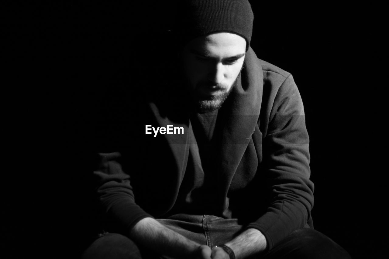 Sad Man Sitting Over Black Background