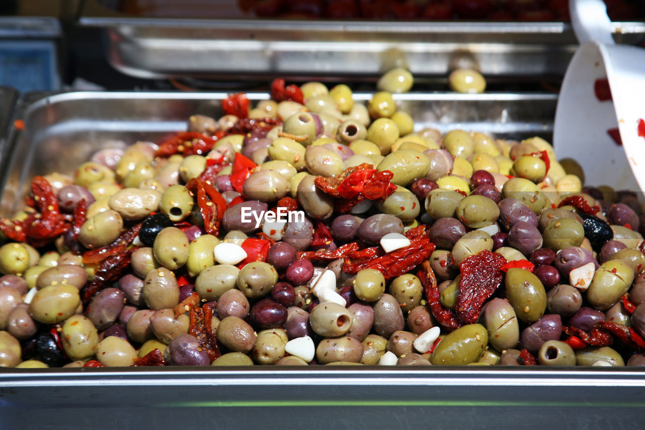 food and drink, food, olive, freshness, indoors, large group of objects, abundance, wellbeing, still life, healthy eating, no people, for sale, retail, fruit, close-up, container, choice, market stall, green olive, business, tray, retail display