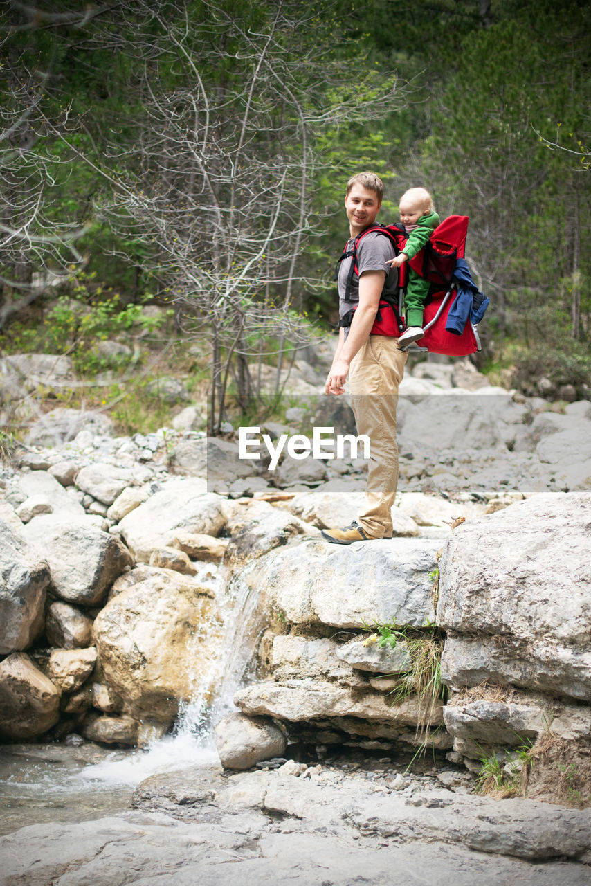 Young man hiking with his baby sitting in the backpack. family is watching small waterfall in forest
