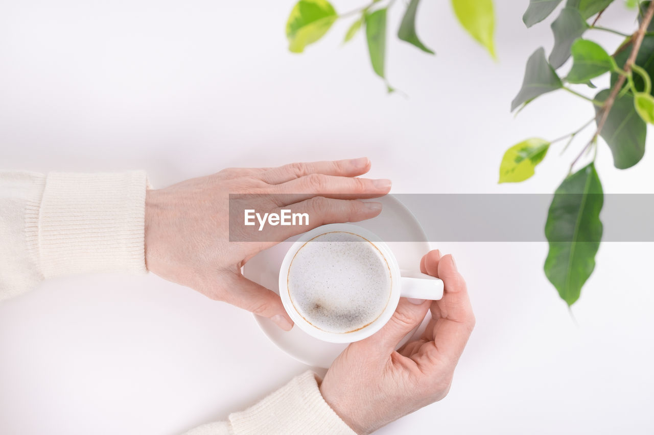 CROPPED IMAGE OF HAND HOLDING COFFEE CUP WITH SPOON AND WHITE BACKGROUND