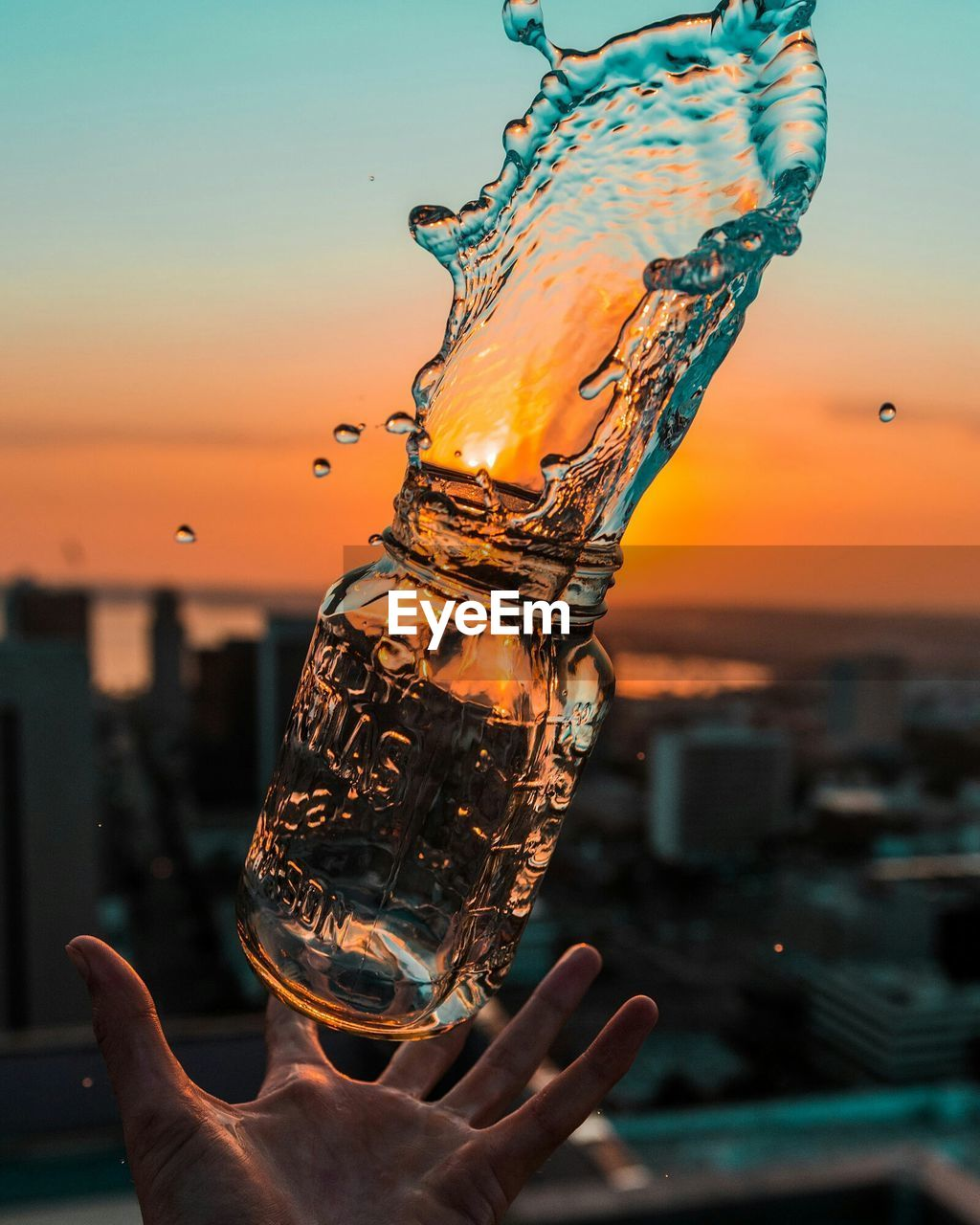 Cropped Image Of Hand Catching Bottle With Splashed Water Against Sky During Sunset