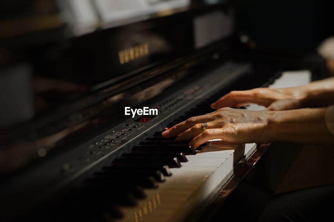 Cropped Hands Of Woman Playing Grand Piano