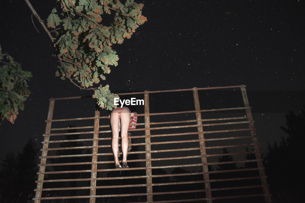 Low Angle View Of Woman Standing On Built Structure At Night