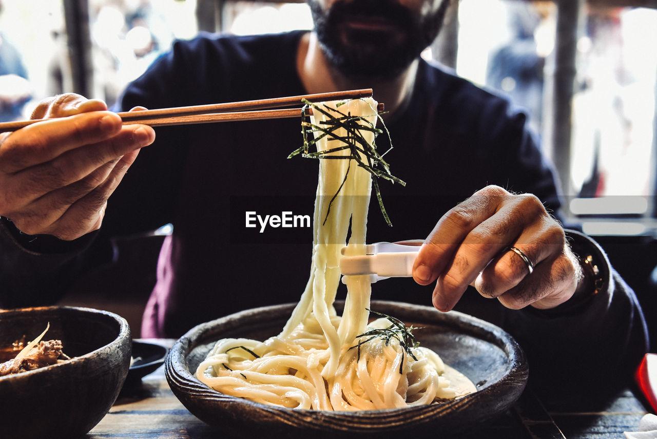 Man eating udon noodles