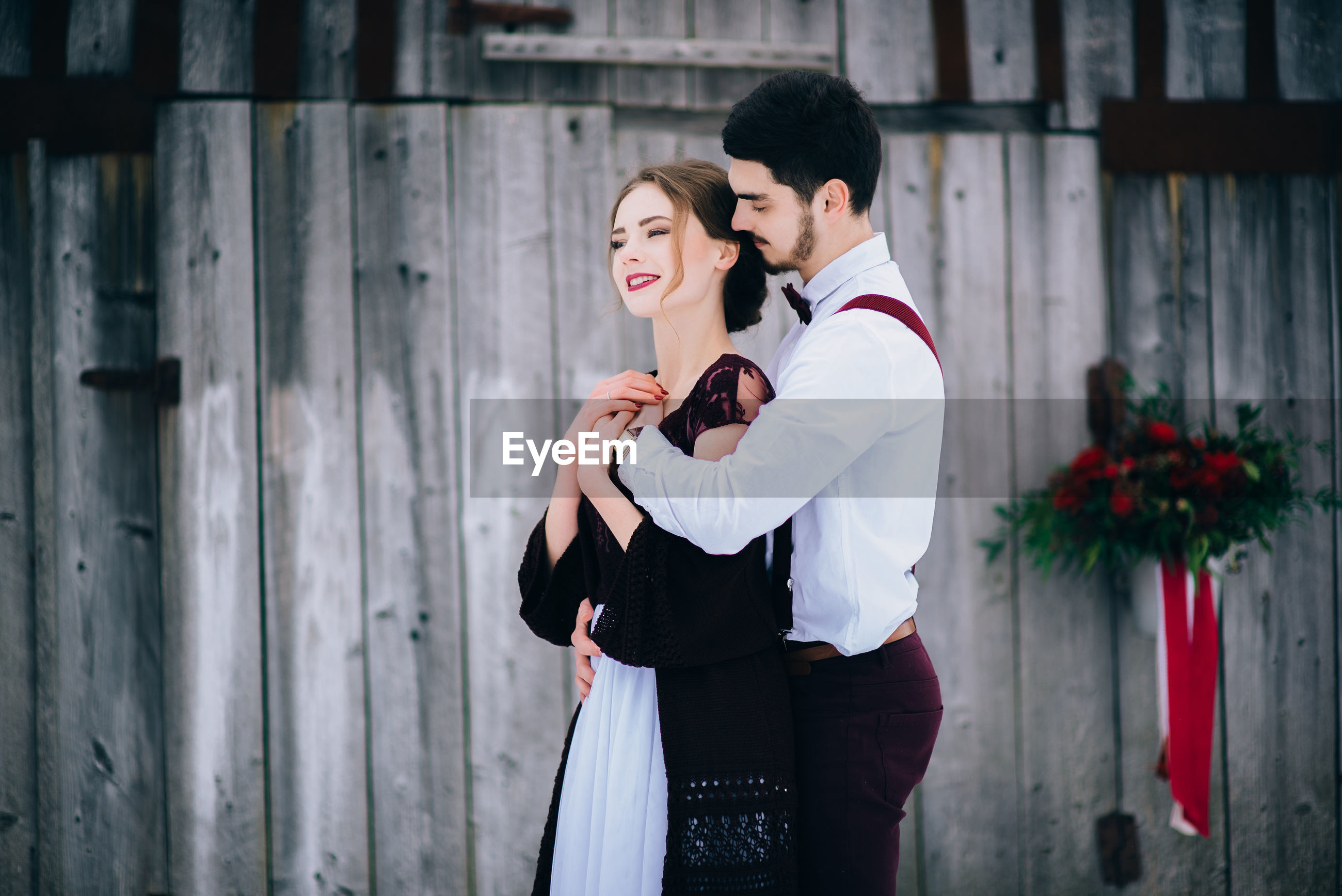 COUPLE STANDING OUTDOORS