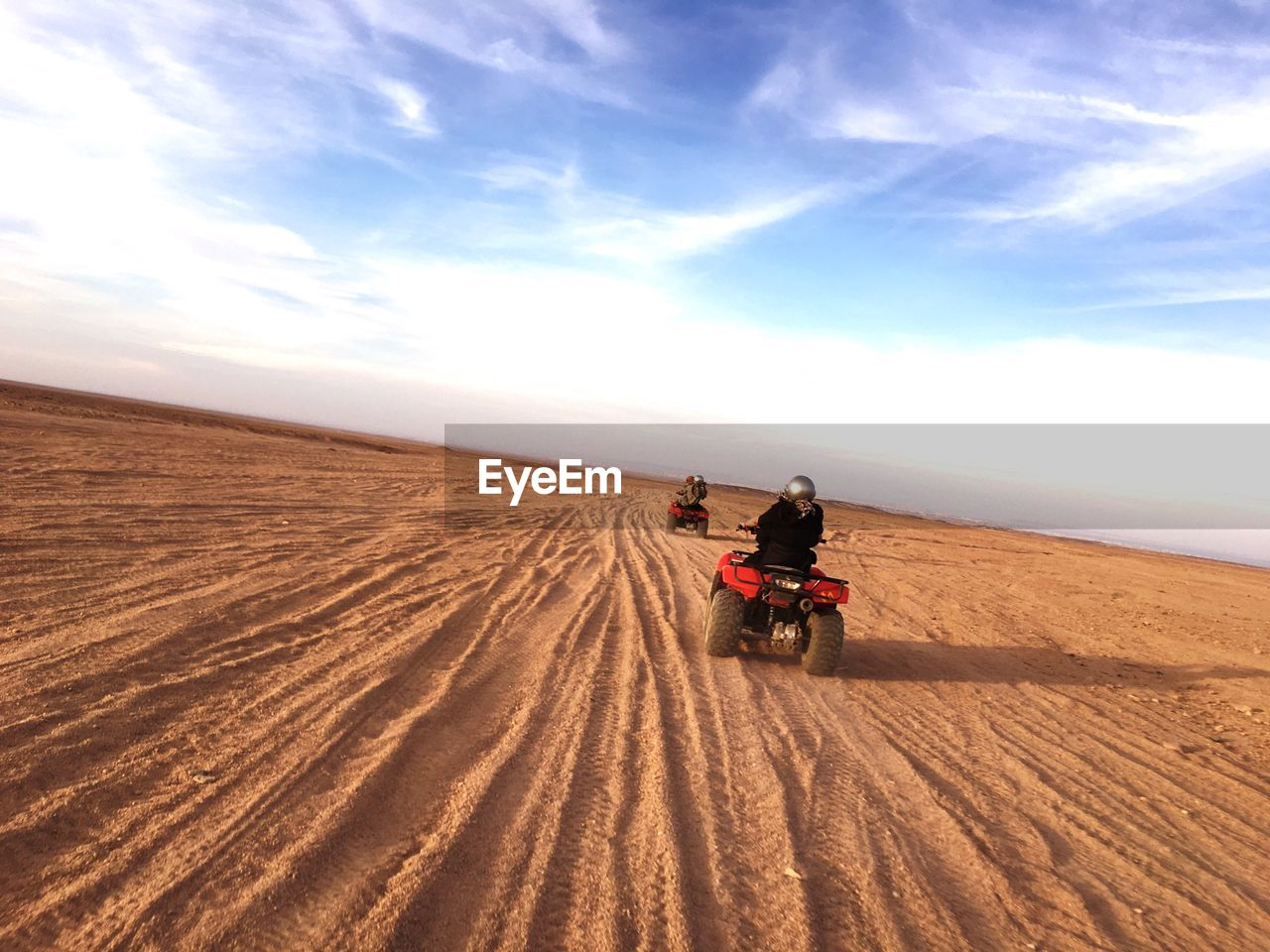 Rear View Of People Riding Quadbikes On Desert