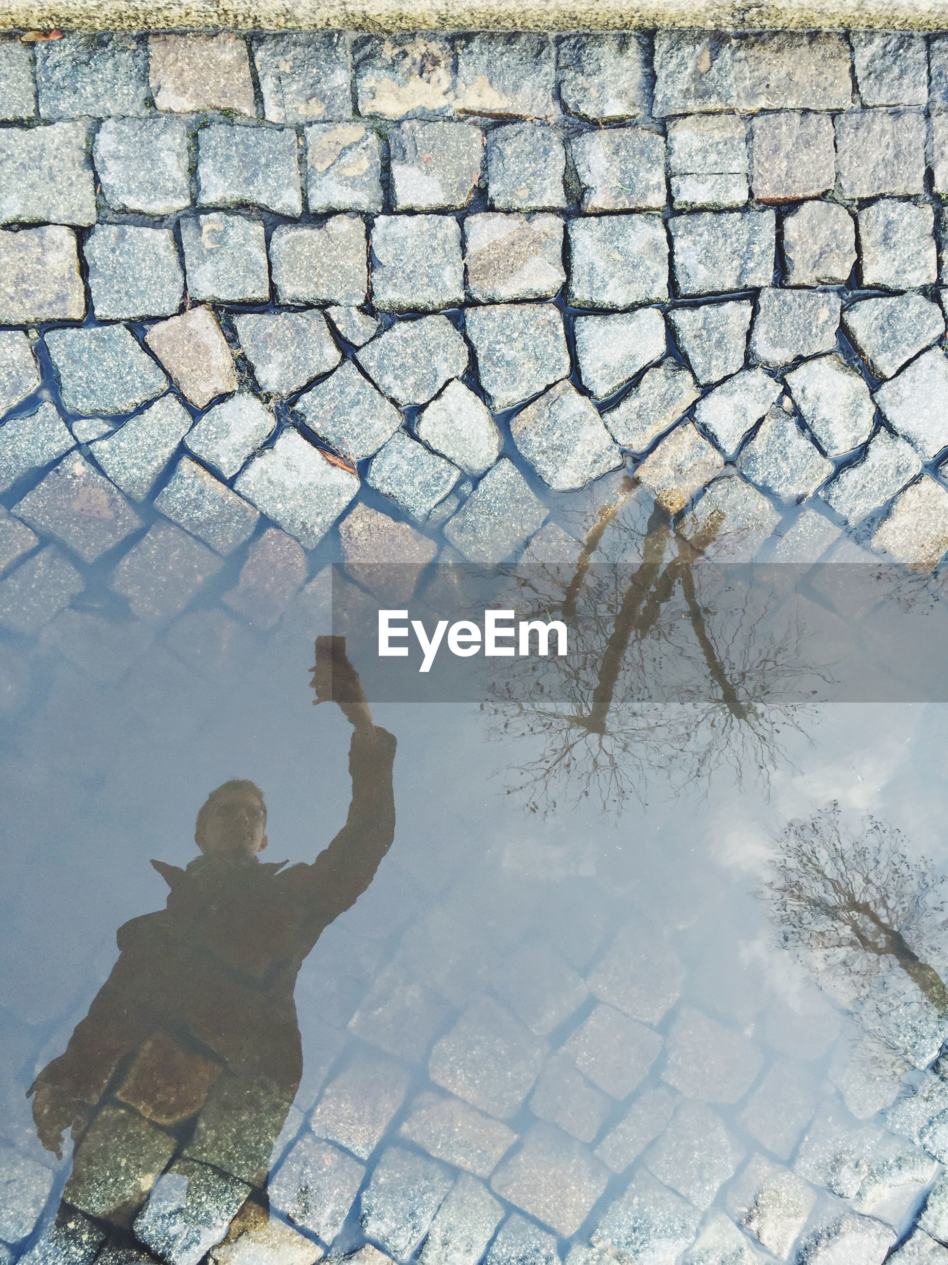 Reflection of man taking selfie in puddle