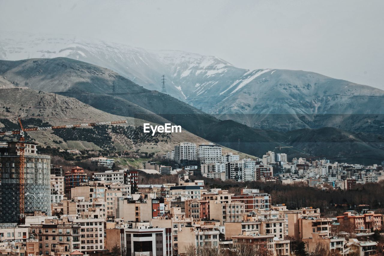 High Angle View Of Buildings By Alborz Mountains Against Sky