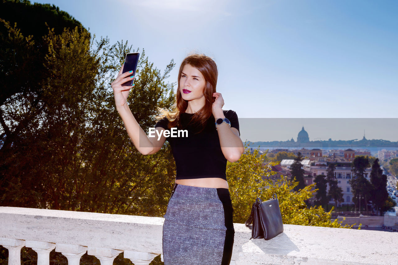 Woman Taking Selfie Through Mobile Phone Against Sky