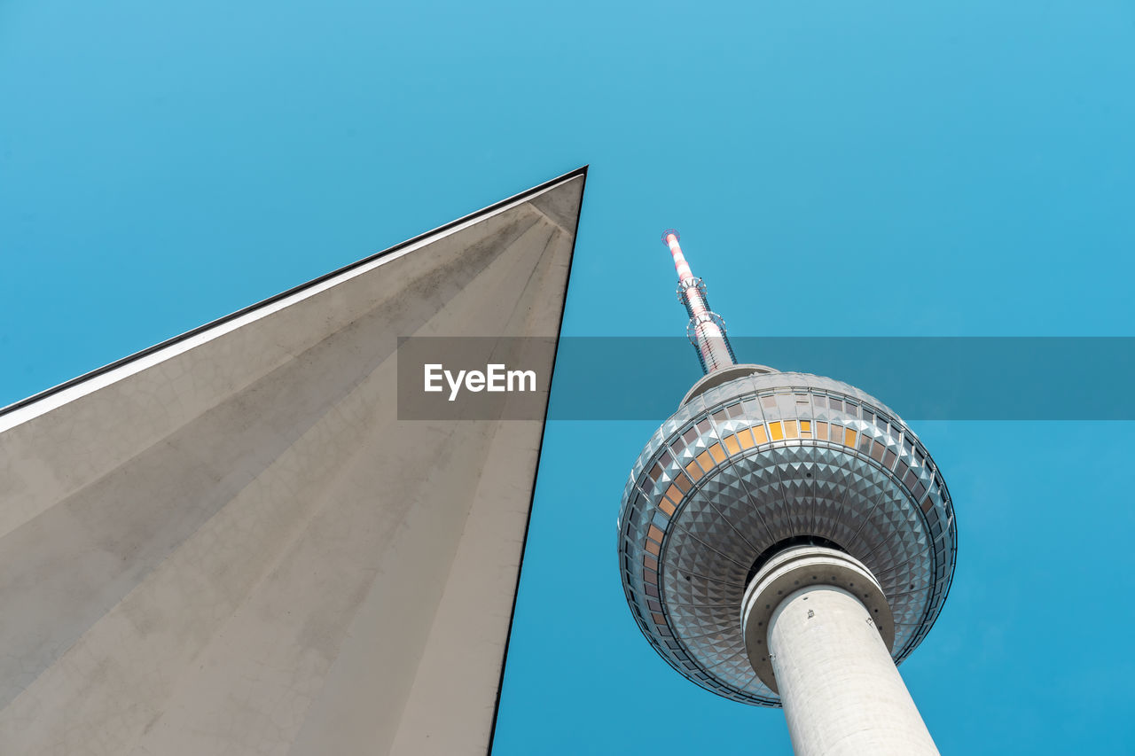 Low angle view of wall and fernsehturm against clear blue sky