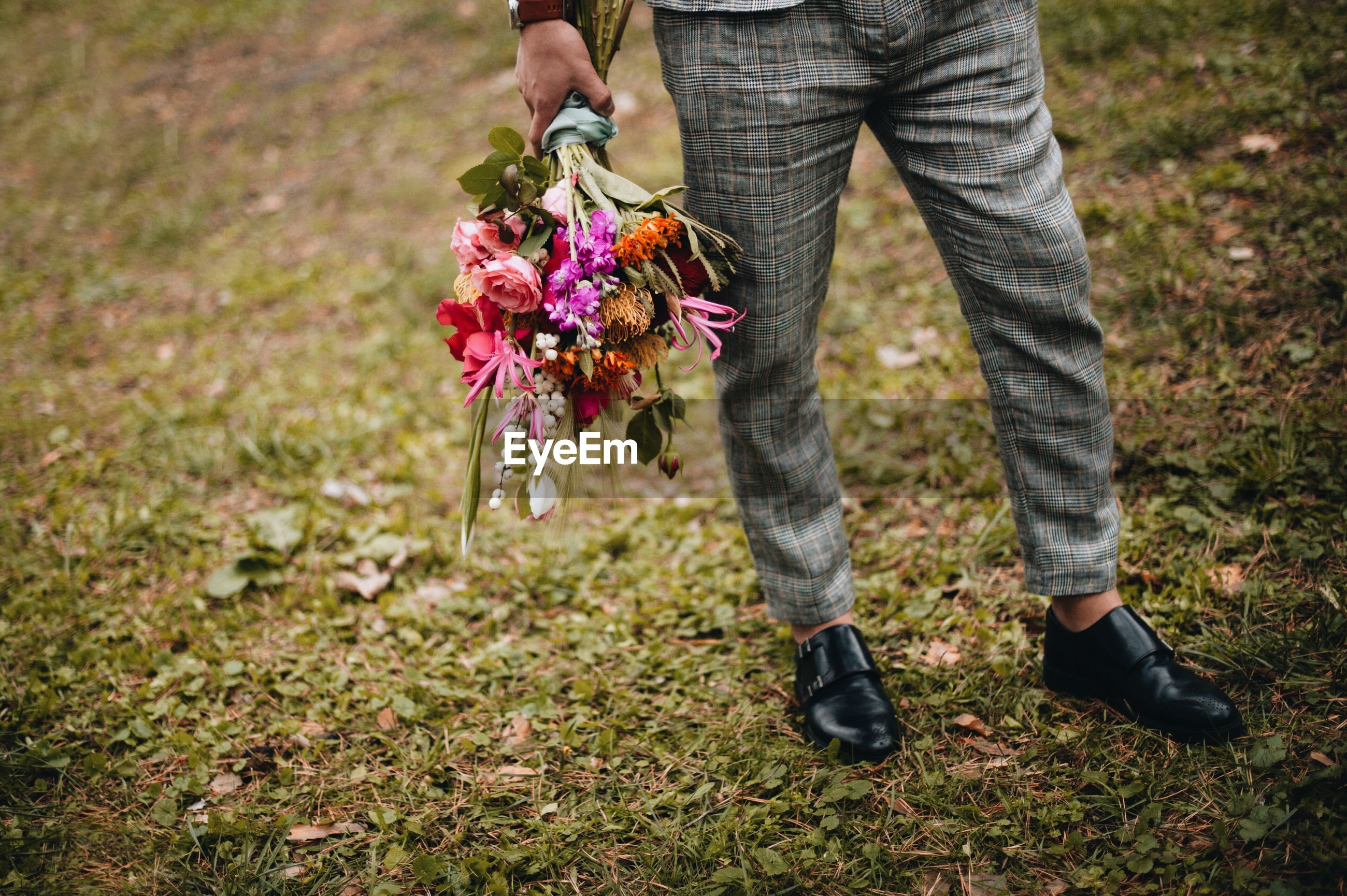 Low section of man holding bouquet while standing on grassy field
