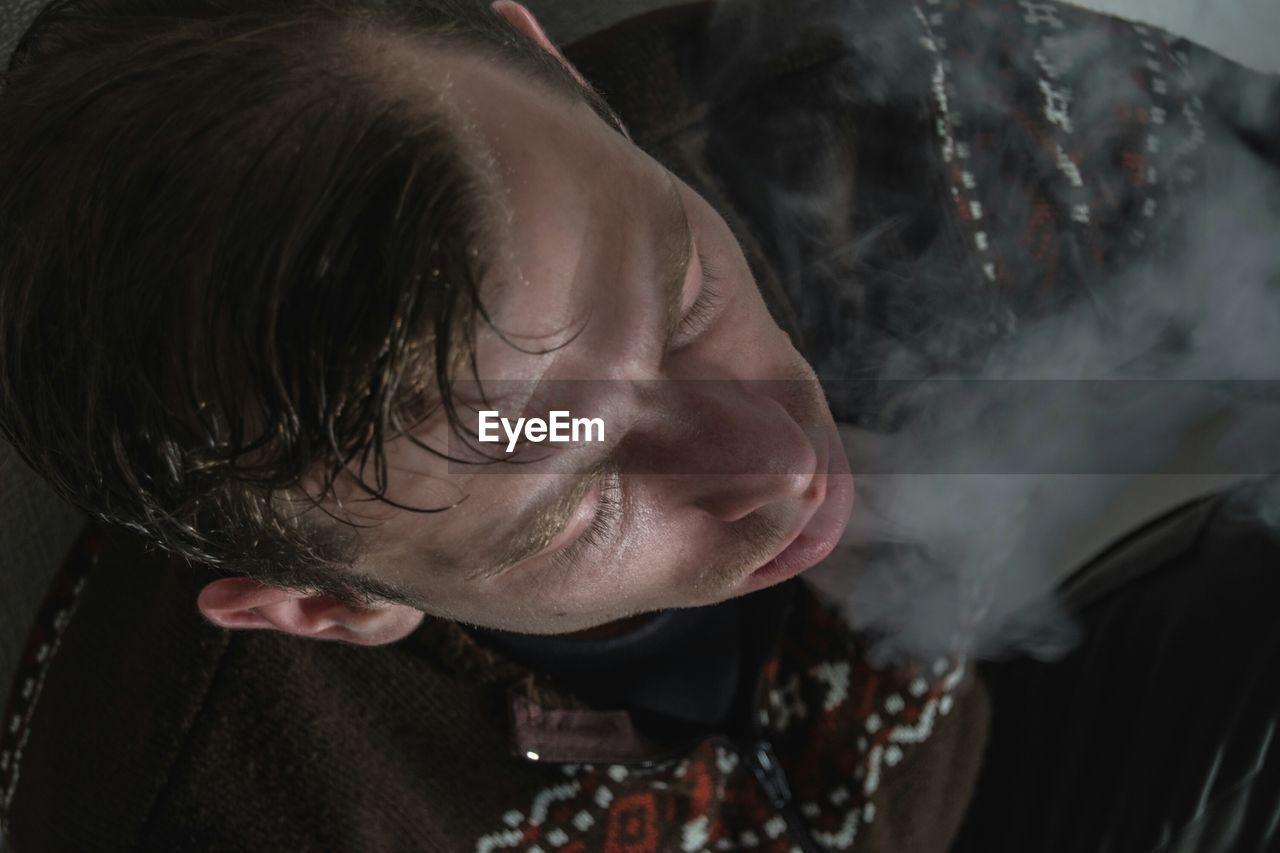 Close-Up Of Man Emitting Smoke