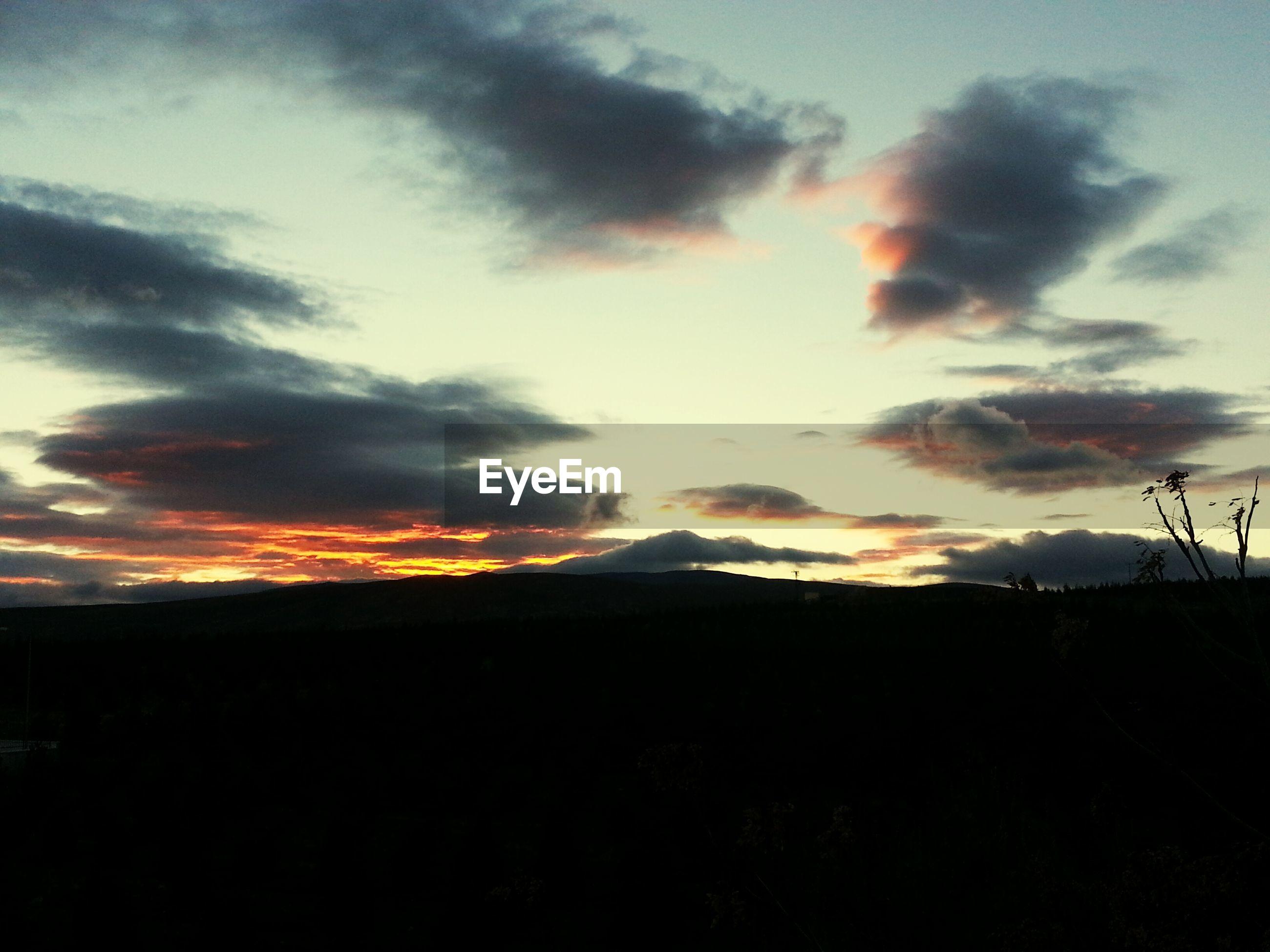 sunset, silhouette, sky, tranquil scene, tranquility, scenics, landscape, beauty in nature, cloud - sky, nature, idyllic, orange color, cloud, cloudy, field, dark, dramatic sky, horizon over land, non-urban scene, dusk
