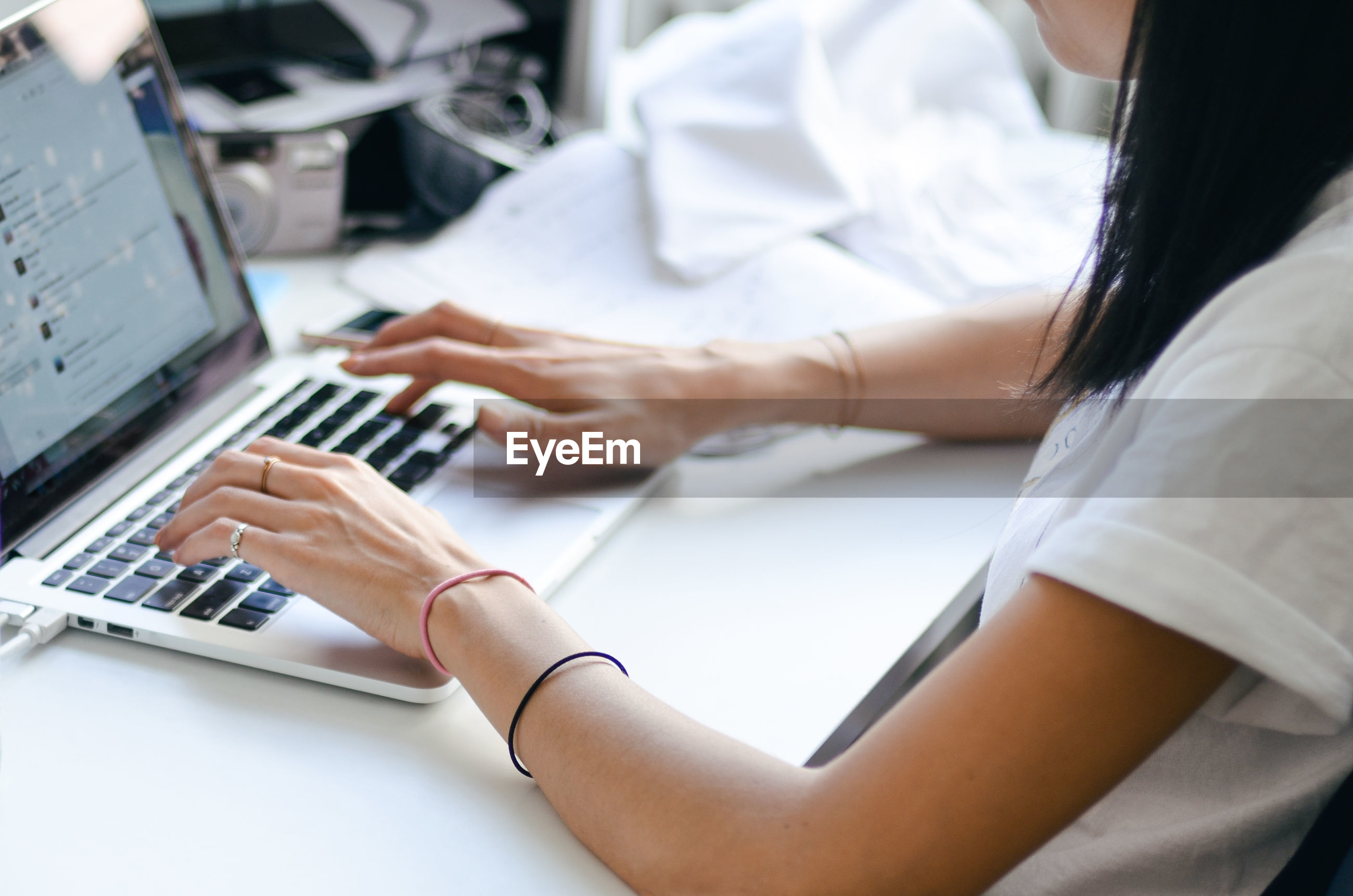 Midsection of woman using laptop at desk in office
