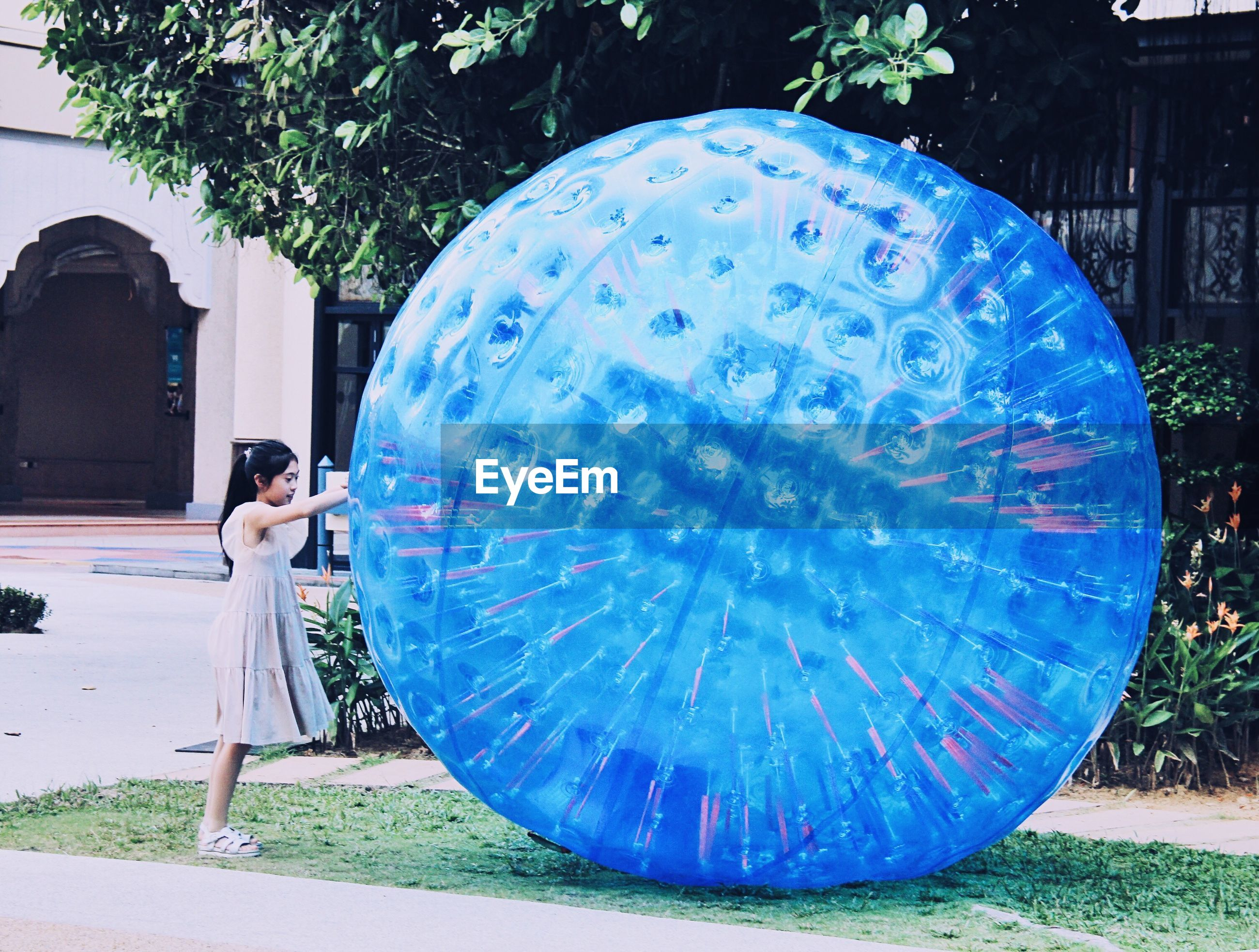 Side view of girl standing by large blue ball at park