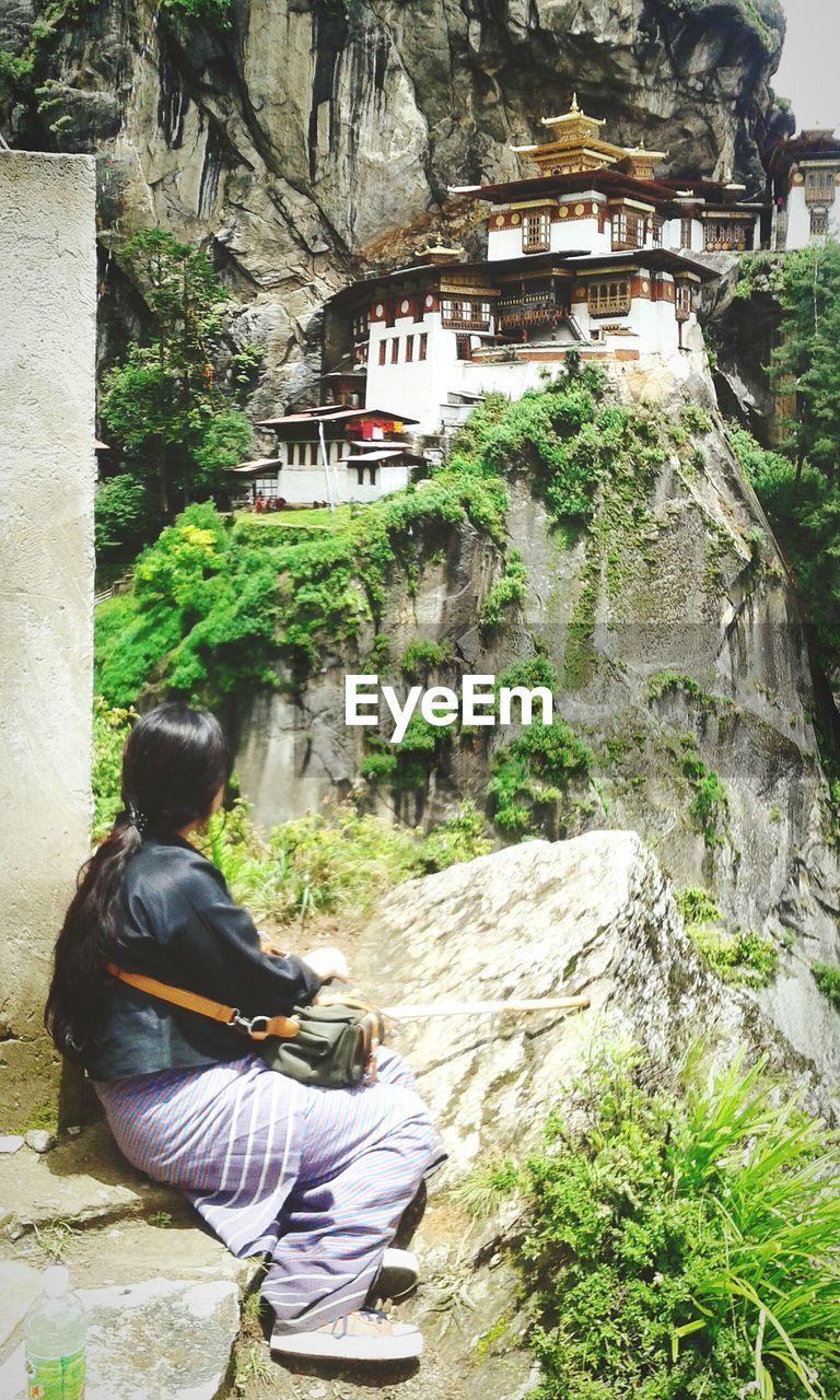 Rear view of woman sitting on rock at taktsang monastery