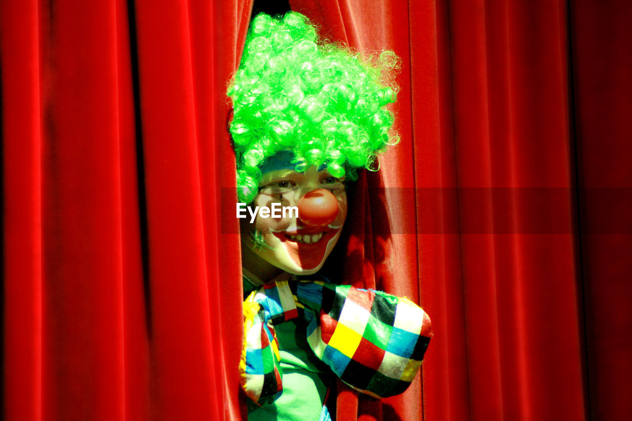 curtain, smiling, looking at camera, happiness, red, portrait, cheerful, one person, stage - performance space, front view, fun, standing, young adult, day, multi colored, outdoors, childhood, real people, young women, clown, close-up, people