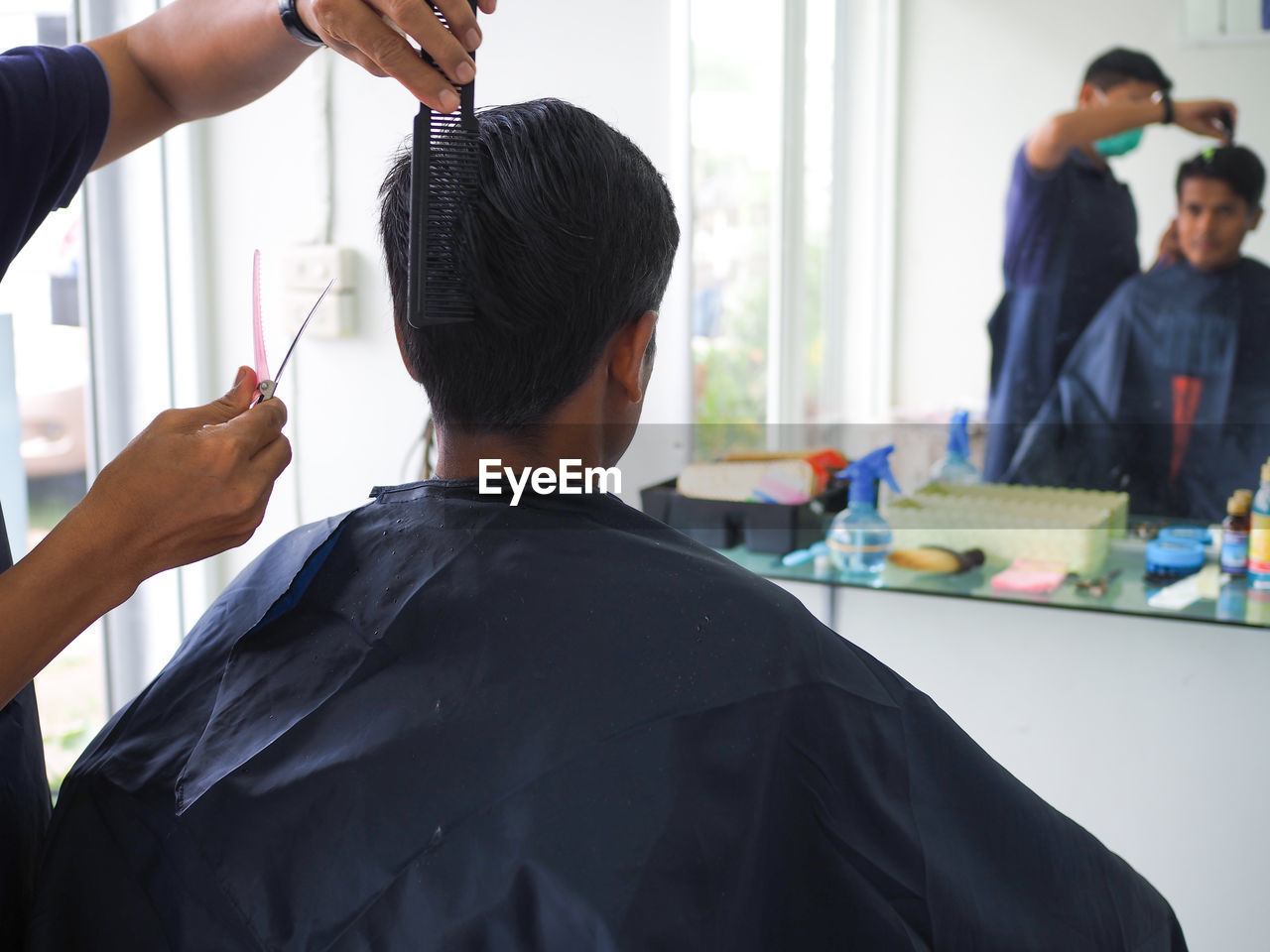 Close-up of barber cutting hair in salon