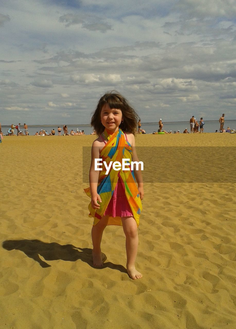Portrait of smiling girl walking on sand at beach against sky