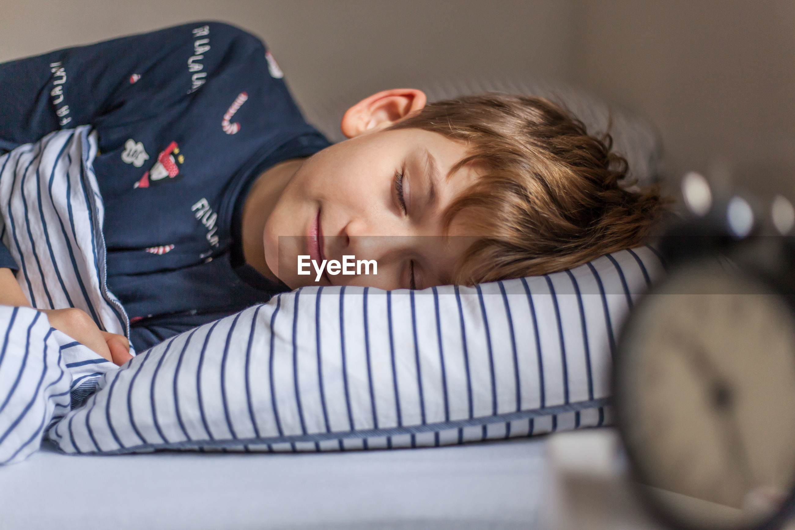 Portrait of boy sleeping on bed at home