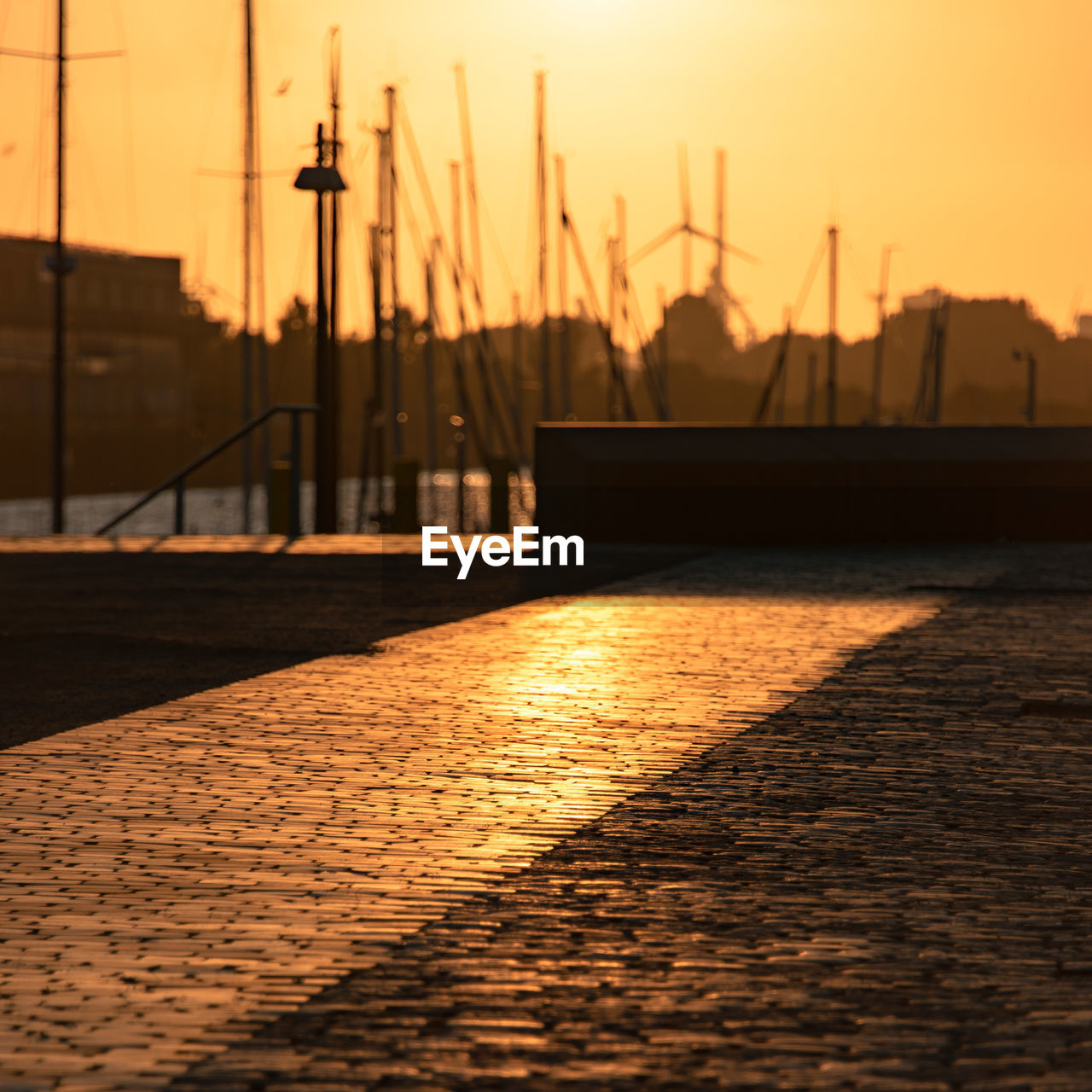 sunset, sky, water, silhouette, nature, orange color, transportation, reflection, sunlight, no people, outdoors, architecture, built structure, sun, nautical vessel, focus on foreground, harbor, beauty in nature, sea