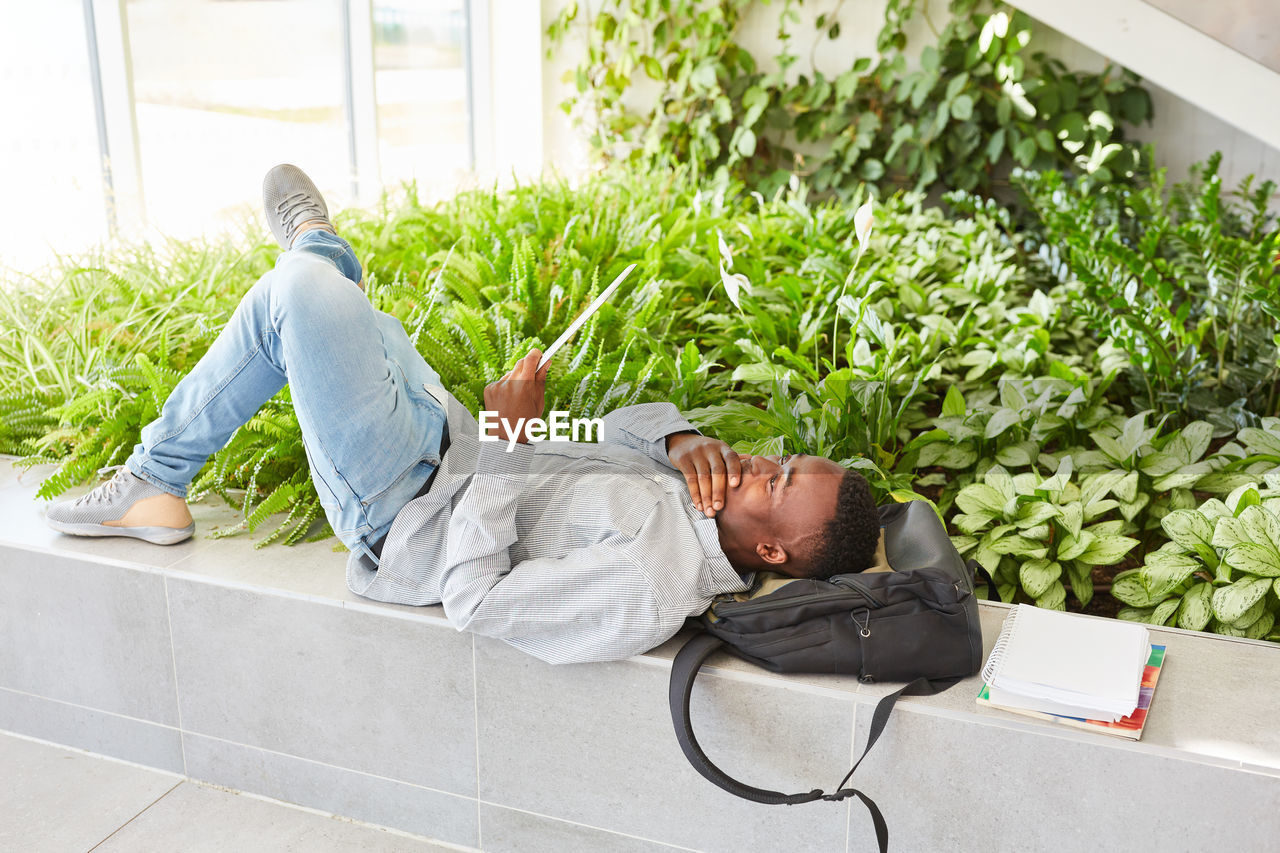 relaxation, plant, lying down, sleeping, one person, leisure activity, lifestyles, day, resting, eyes closed, men, casual clothing, full length, nature, adult, side view, young adult, real people, outdoors, napping