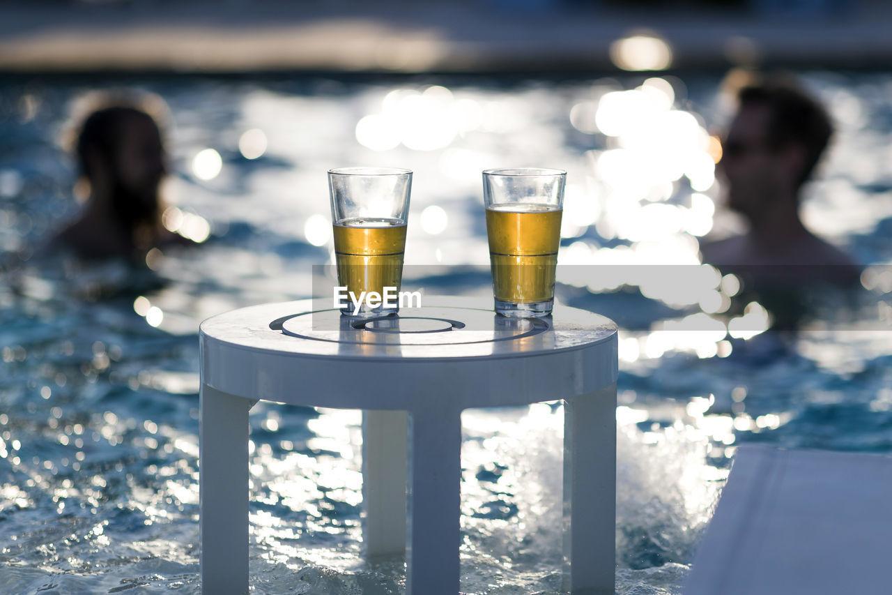 Beer Glasses On Table Against Swimming Pool
