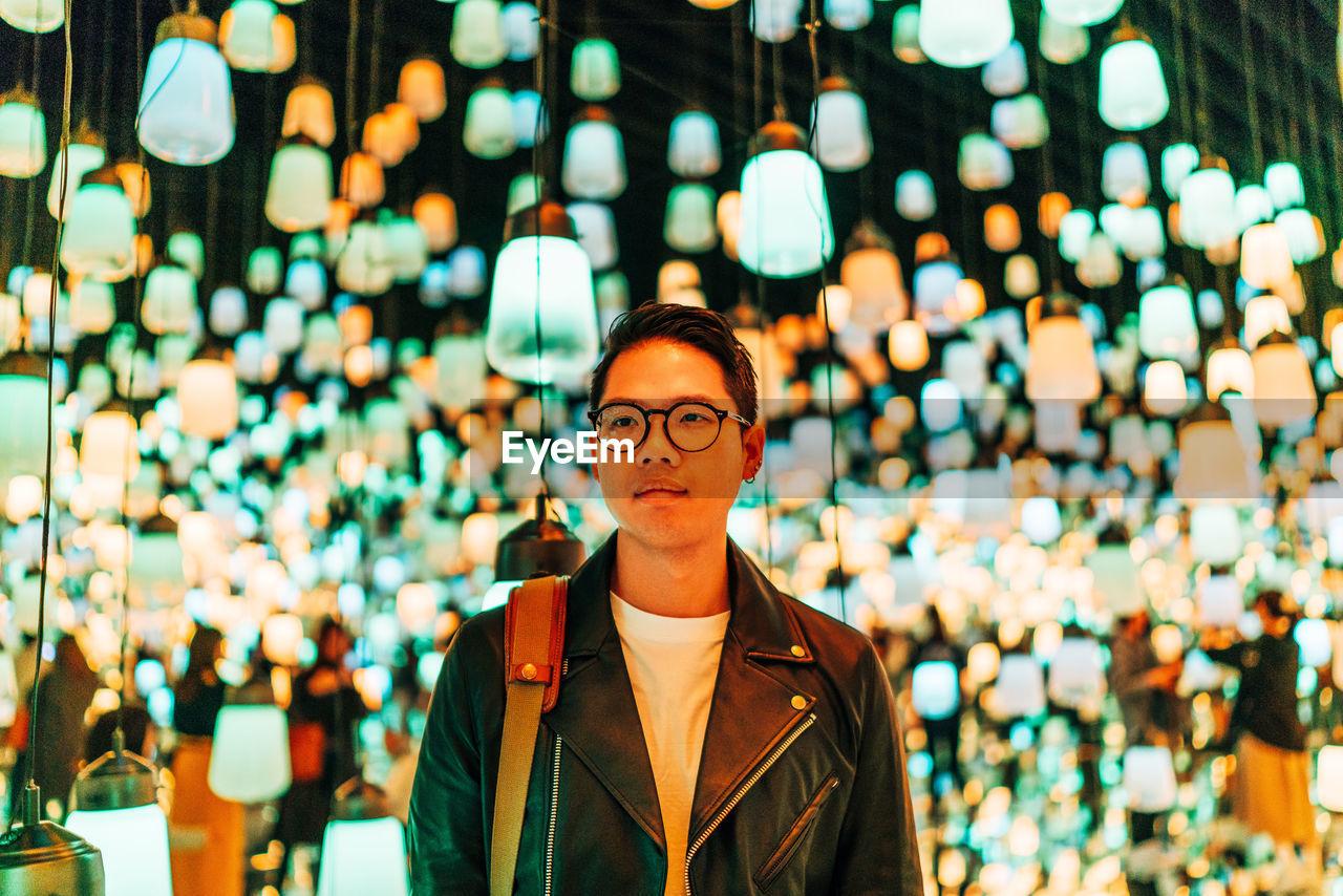 Young Man Looking Away While Standing Against Illuminated Lights