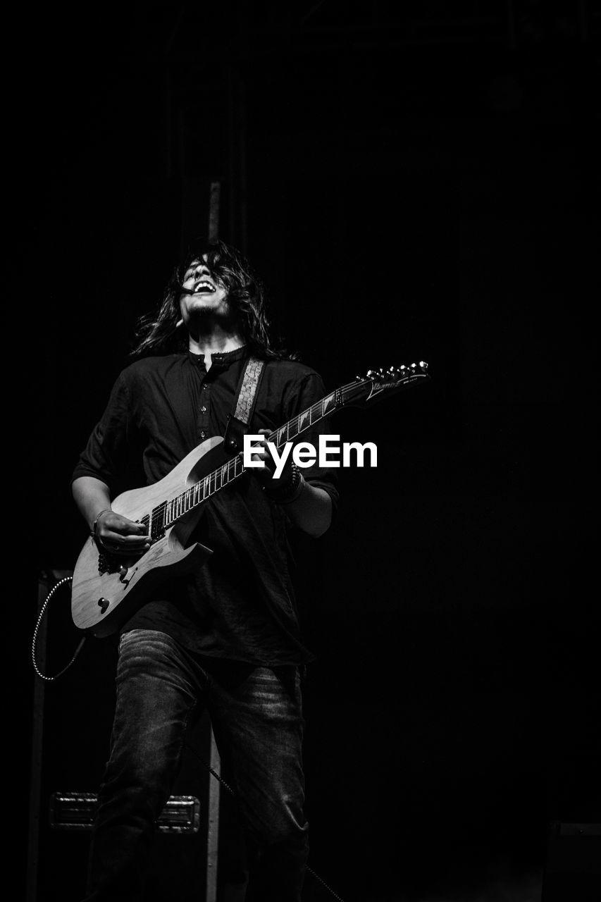 Singer playing guitar while singing against black background