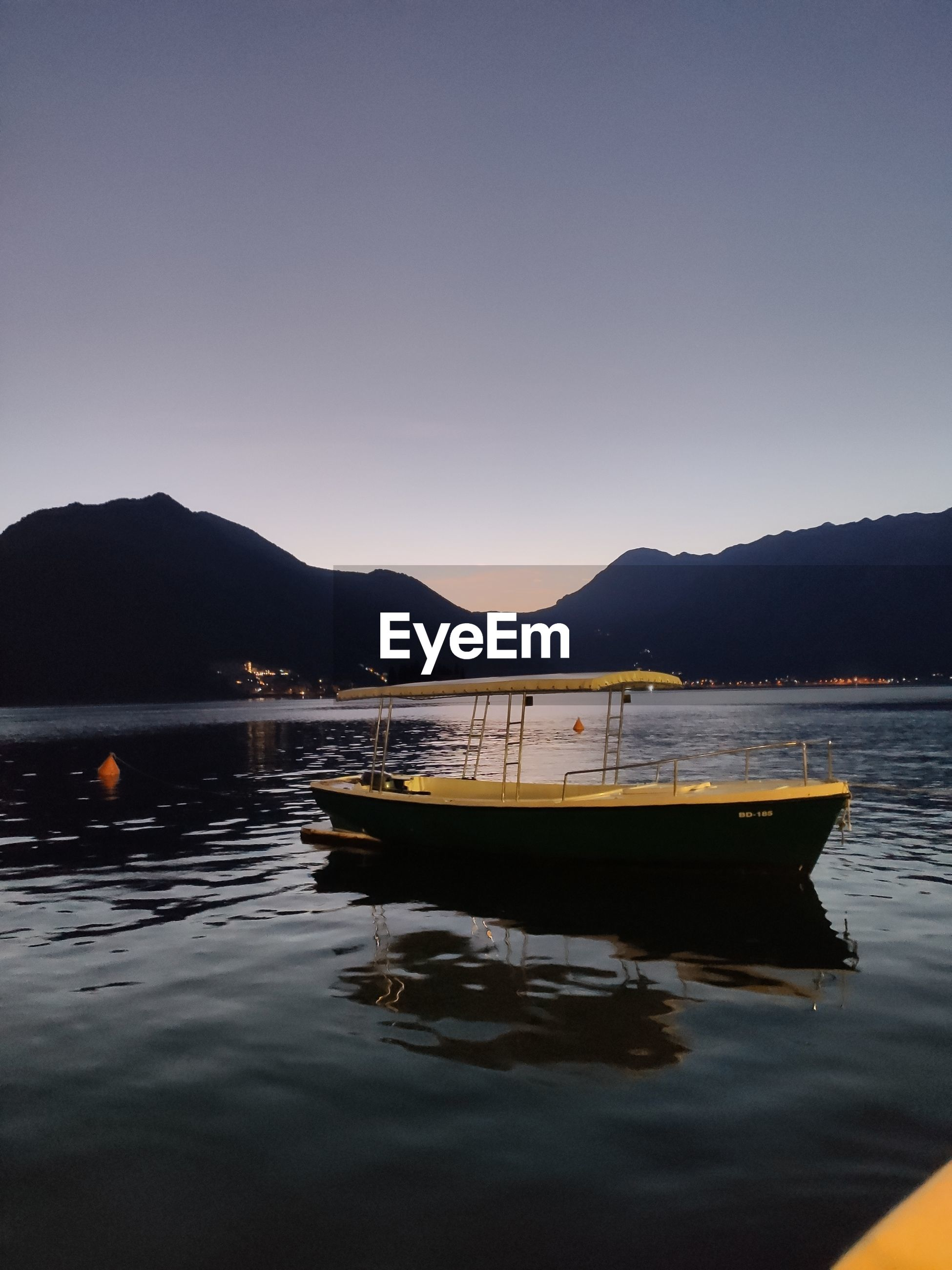 Boat in lake against clear sky during sunset