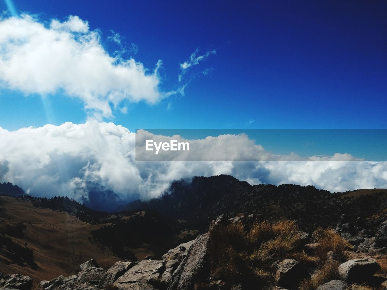cloud - sky, sky, scenics - nature, beauty in nature, tranquil scene, tranquility, mountain, non-urban scene, day, blue, no people, nature, landscape, environment, mountain range, idyllic, outdoors, rock, remote, low angle view, mountain ridge, mountain peak