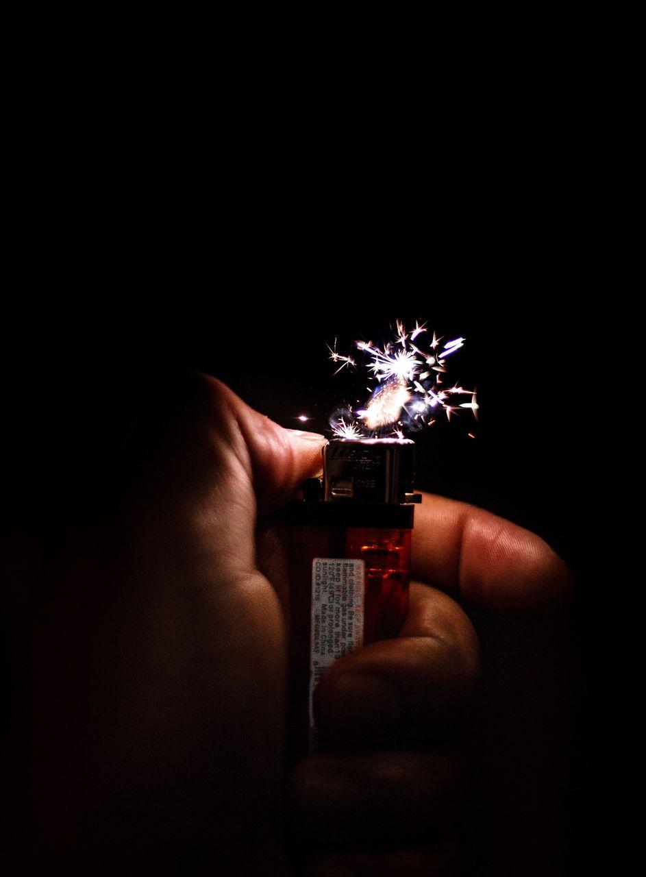 Close-up of hand holding lit cigarette lighter against black background