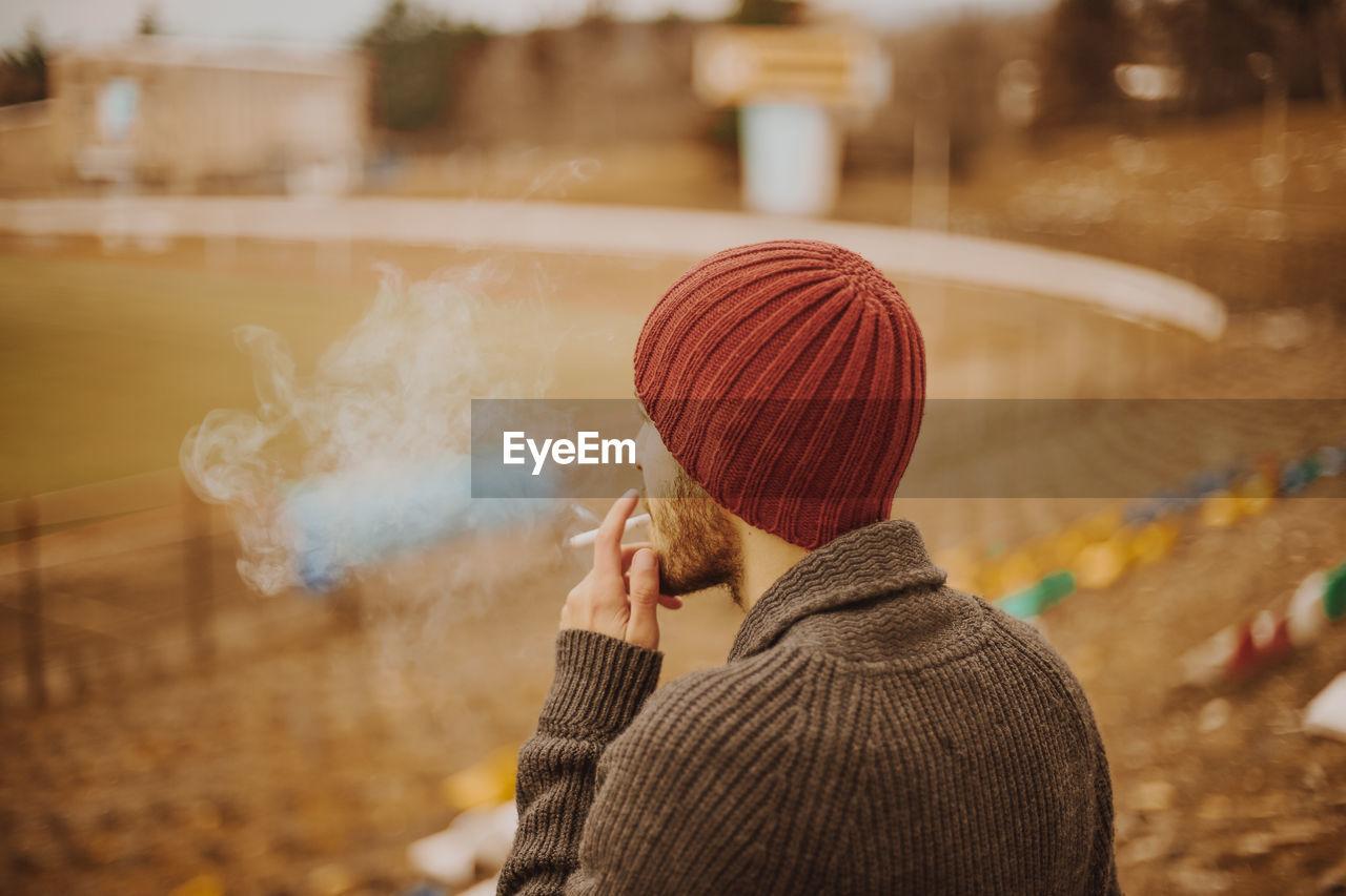 Man wearing warm clothing while smoking cigarette outdoors