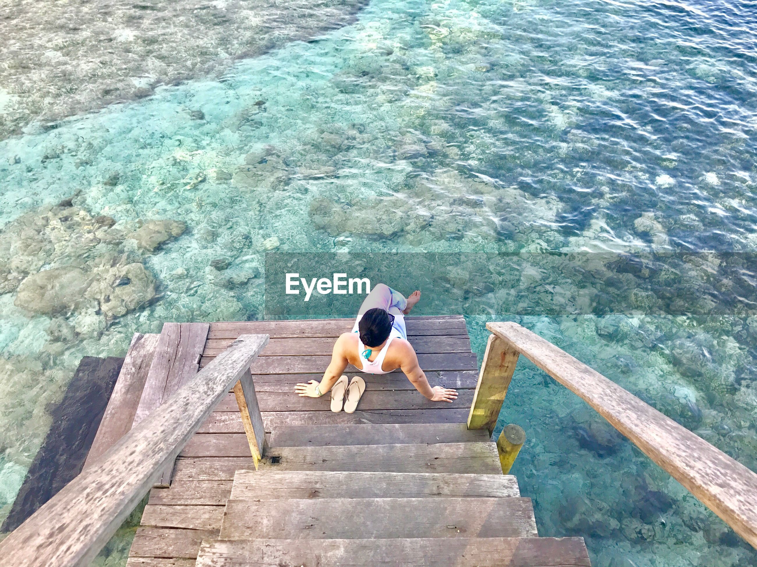 High angle view of man sitting on wooden planks by sea