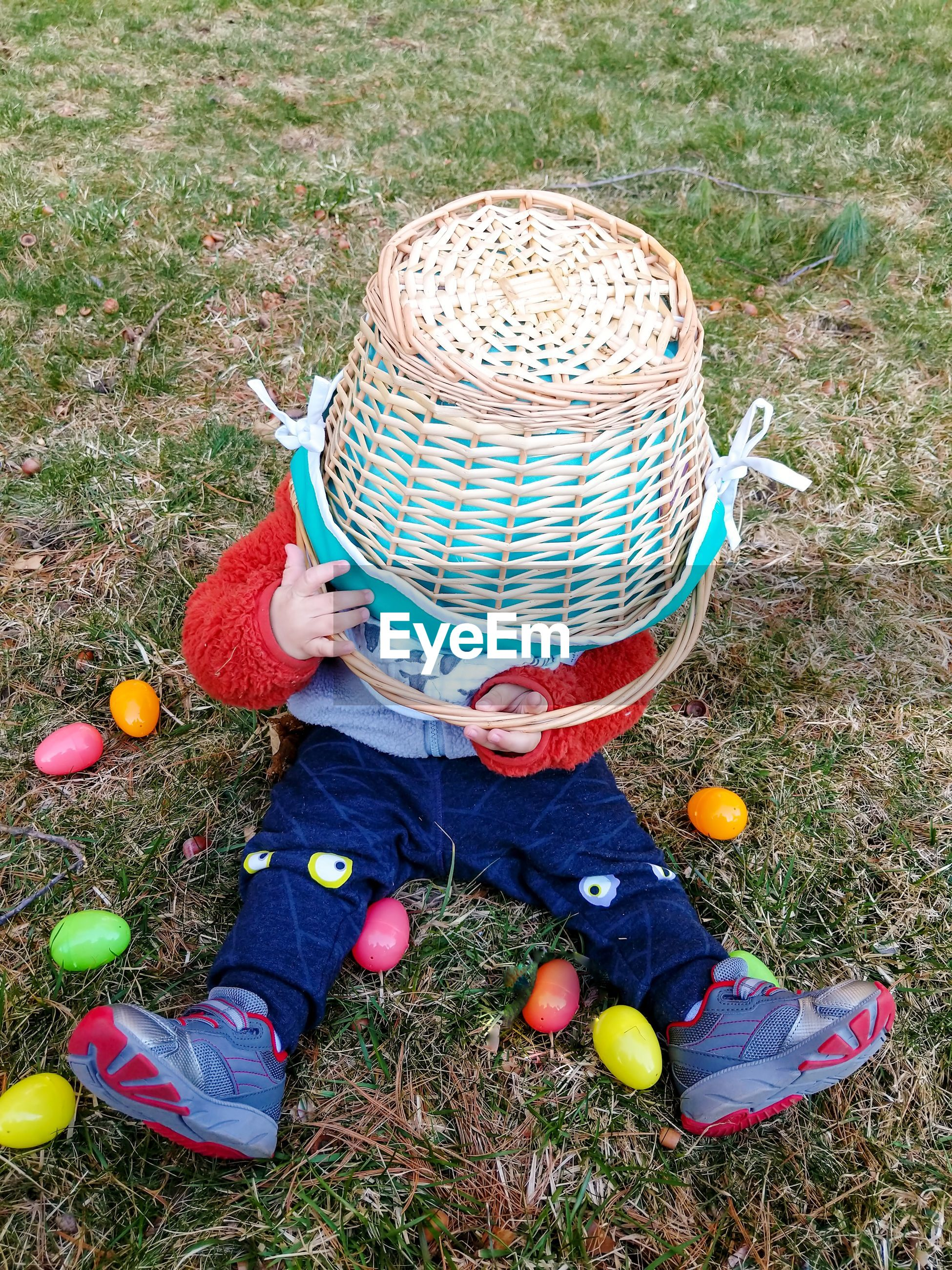 Toddler playing with basket during easter egg hunt