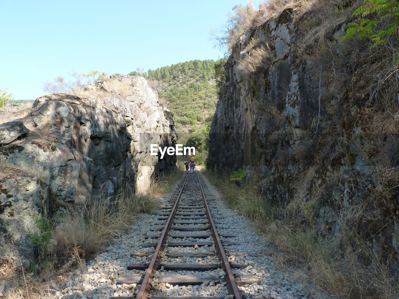 railroad track, rail transportation, rock - object, transportation, day, landscape, nature, mountain, the way forward, outdoors, clear sky, scenics, tree, tranquil scene, beauty in nature, sky, adventure, grass, no people