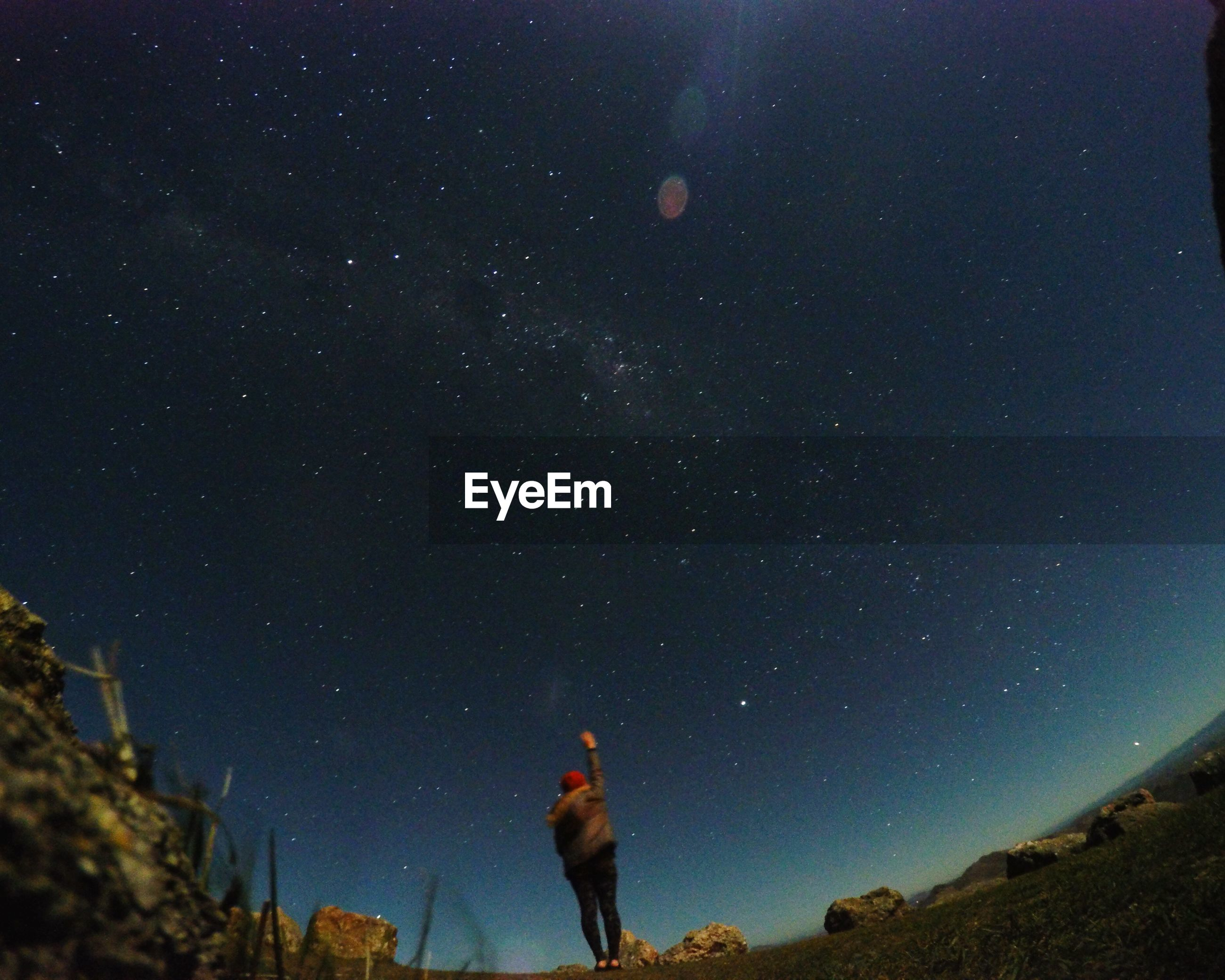 Rear view of person standing with arm raised against starry sky