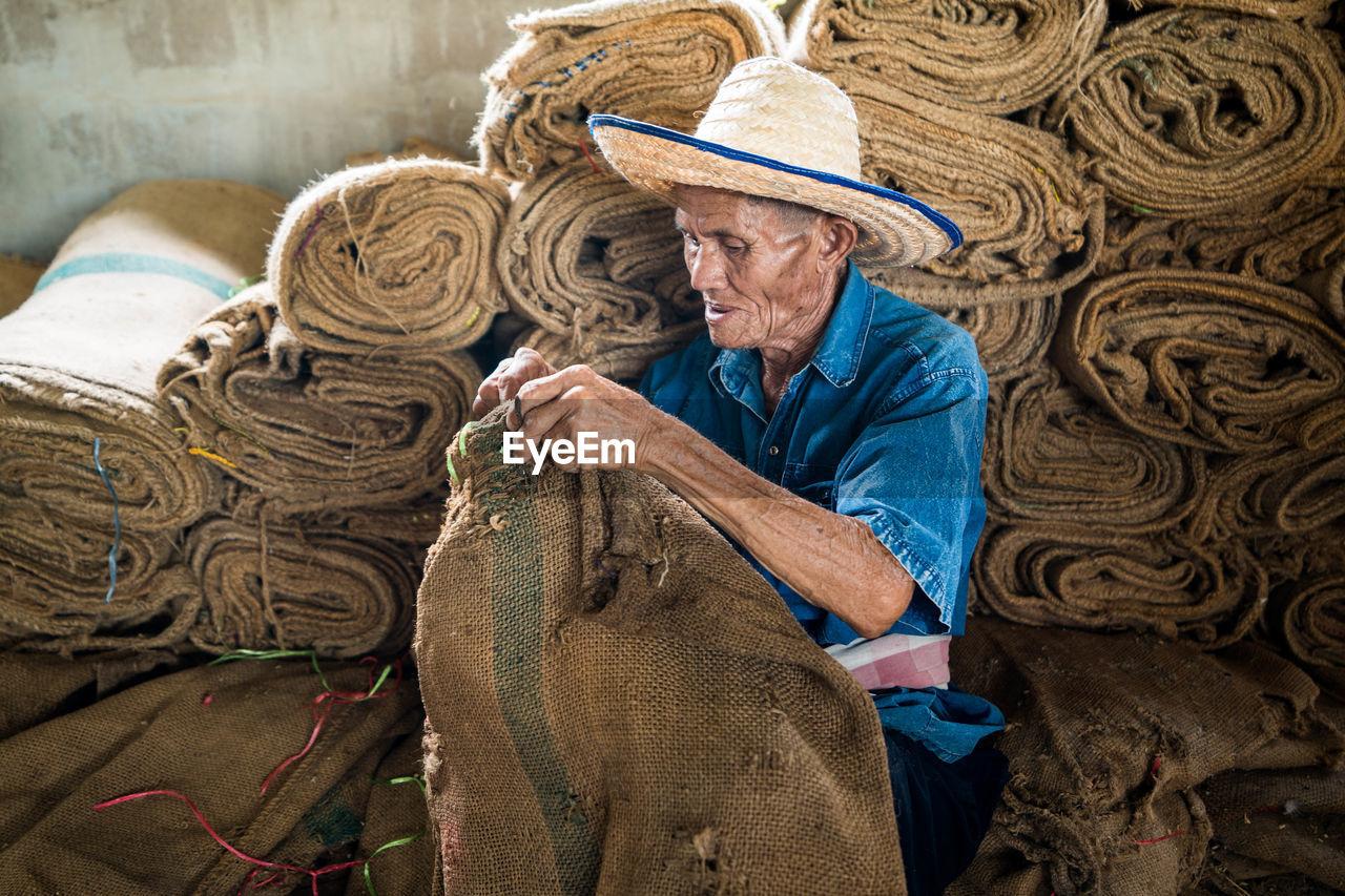 Senior man holding sack in warehouse