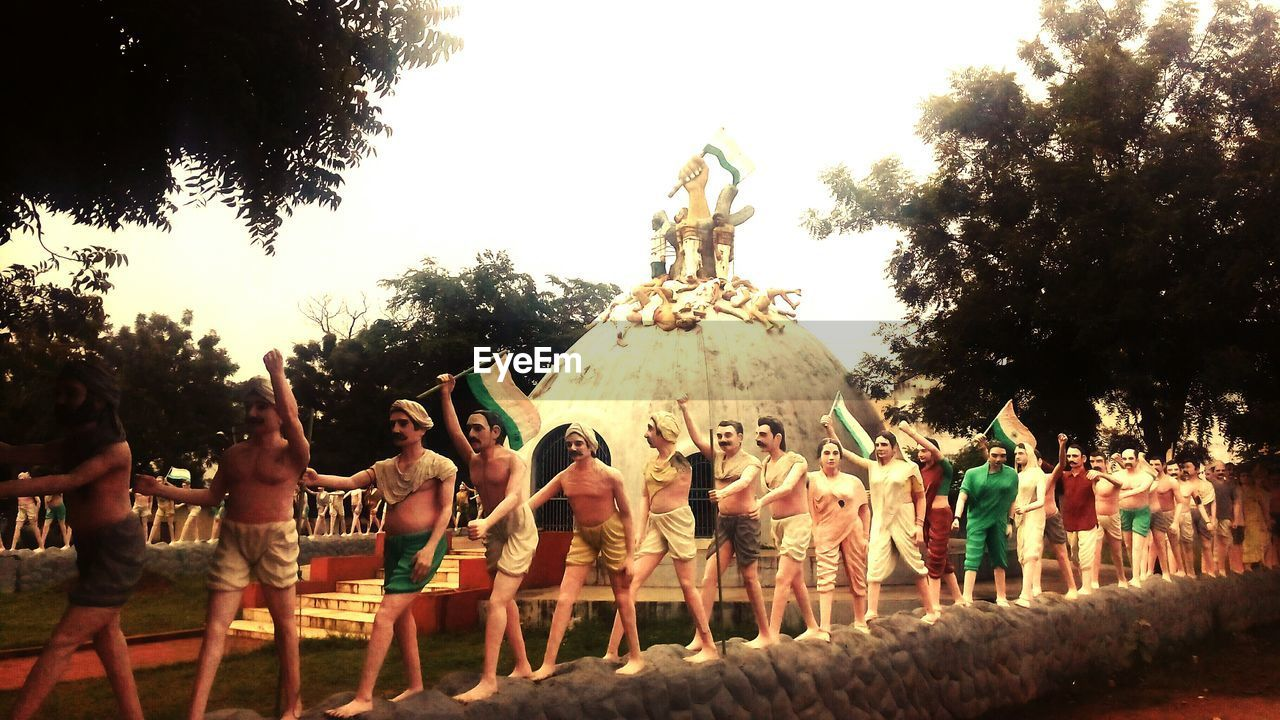 large group of people, tree, sculpture, men, statue, spirituality, outdoors, togetherness, women, real people, day, sky, people