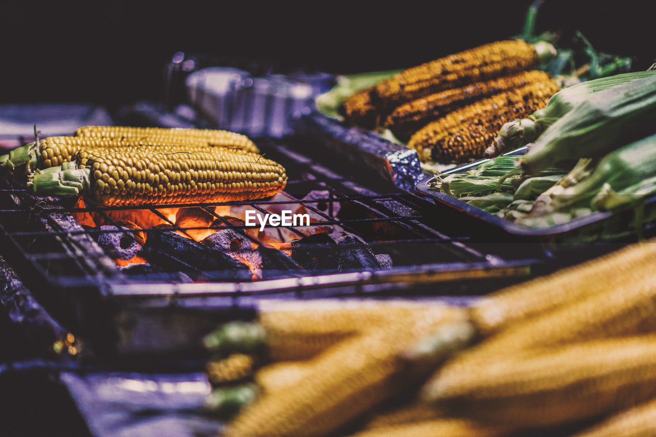 Close-Up Of Corns Being Cooked On Barbecue Grill